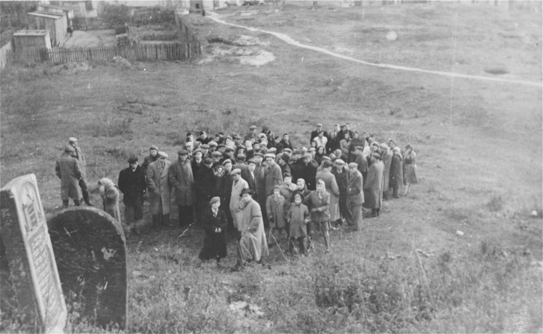 Survivors from Ostrowiec walk toward the site of a mass grave for 2000 Jews shot during the October 1942 action.    In the foreground is a portion of the vandalized Jewish cemetery.