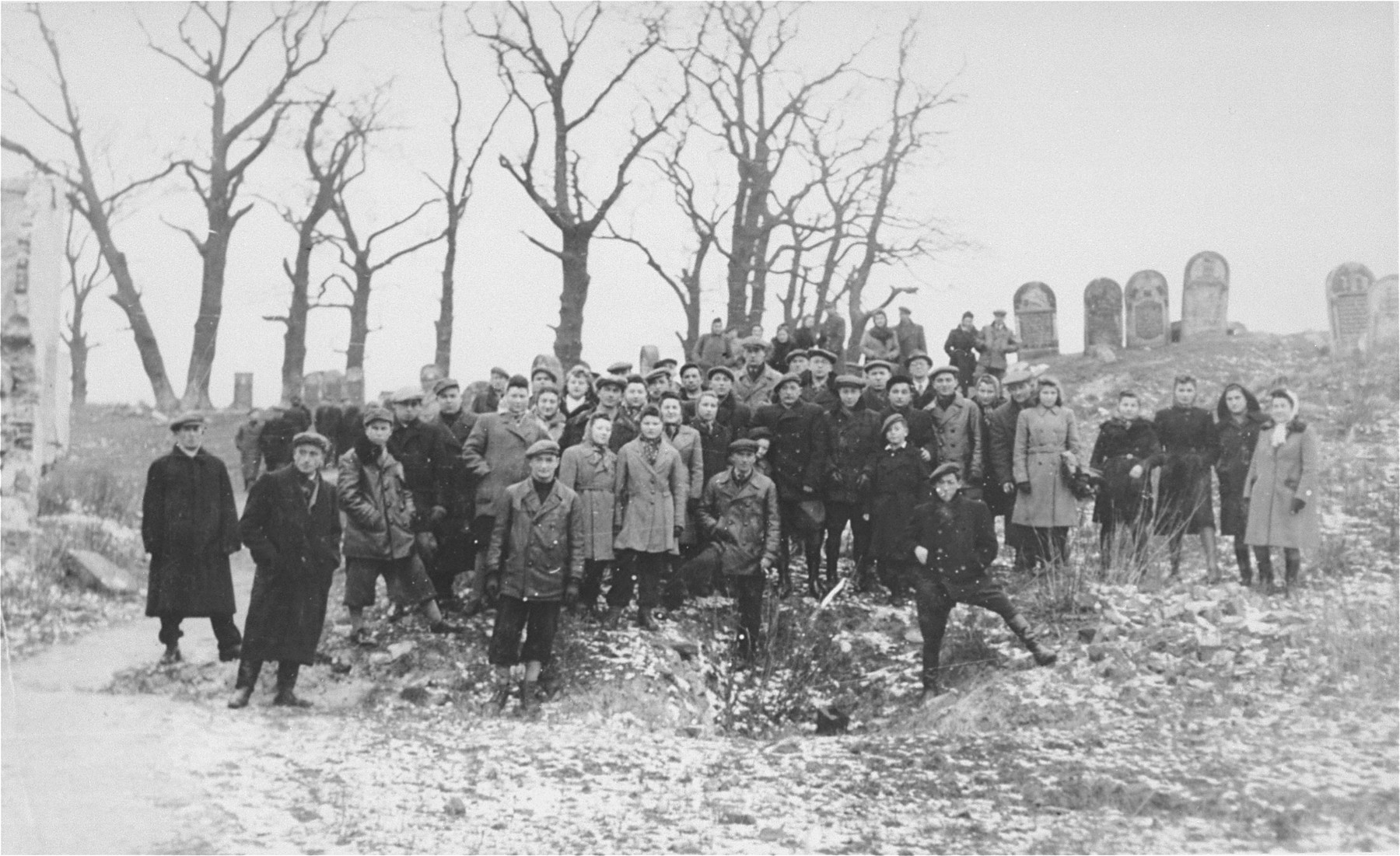 Group portrait of Jews from Ostrowiec standing on the site of a mass grave for 2000 Jews shot during the October 1942 action.  Behind them is a portion of the vandalized Jewish cemetery.    Among those pictured is Berek Blumensztok.  He is standing in the center. Berek  returned to Ostrowiec after the war with the hope of reuniting with his family.  However, all had perished, including his mother, father and 8 siblings.   Also pictured is Dora Weinberg Berman (third woman from the right).