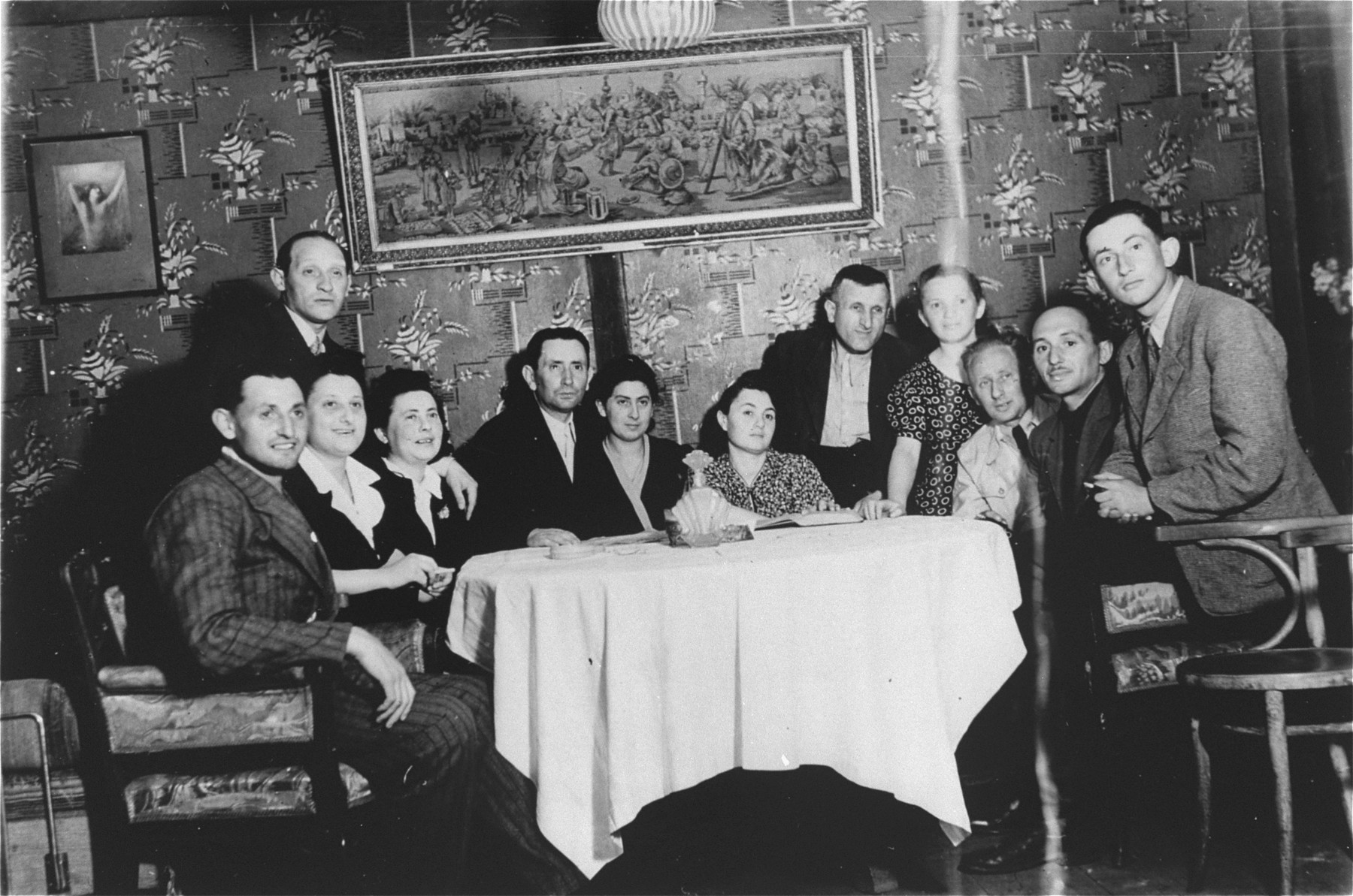The family of Sylvia Kramarski gathers in their former home in Tarczyn, Poland.     Sylvia Kramarski is pictured second from the left.  She notes that their house was largely undisturbed during their absence and that surviving family members lived there for a month in the winter of 1945.  A few months later it was stoned by local residents.
