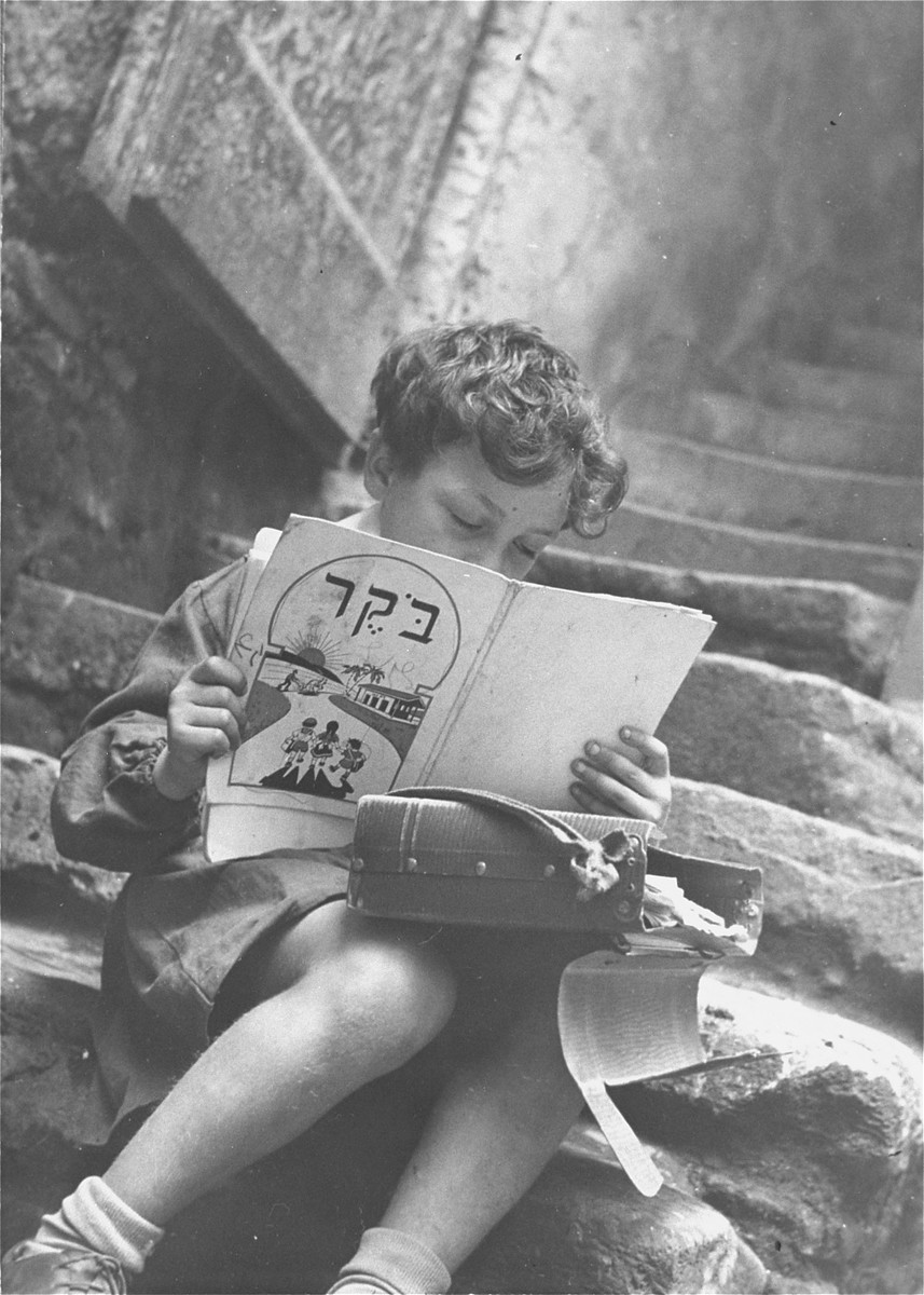 A young Jewish boy studies his Hebrew reading book on the steps of his house in the old Jewish quarter of Rome.