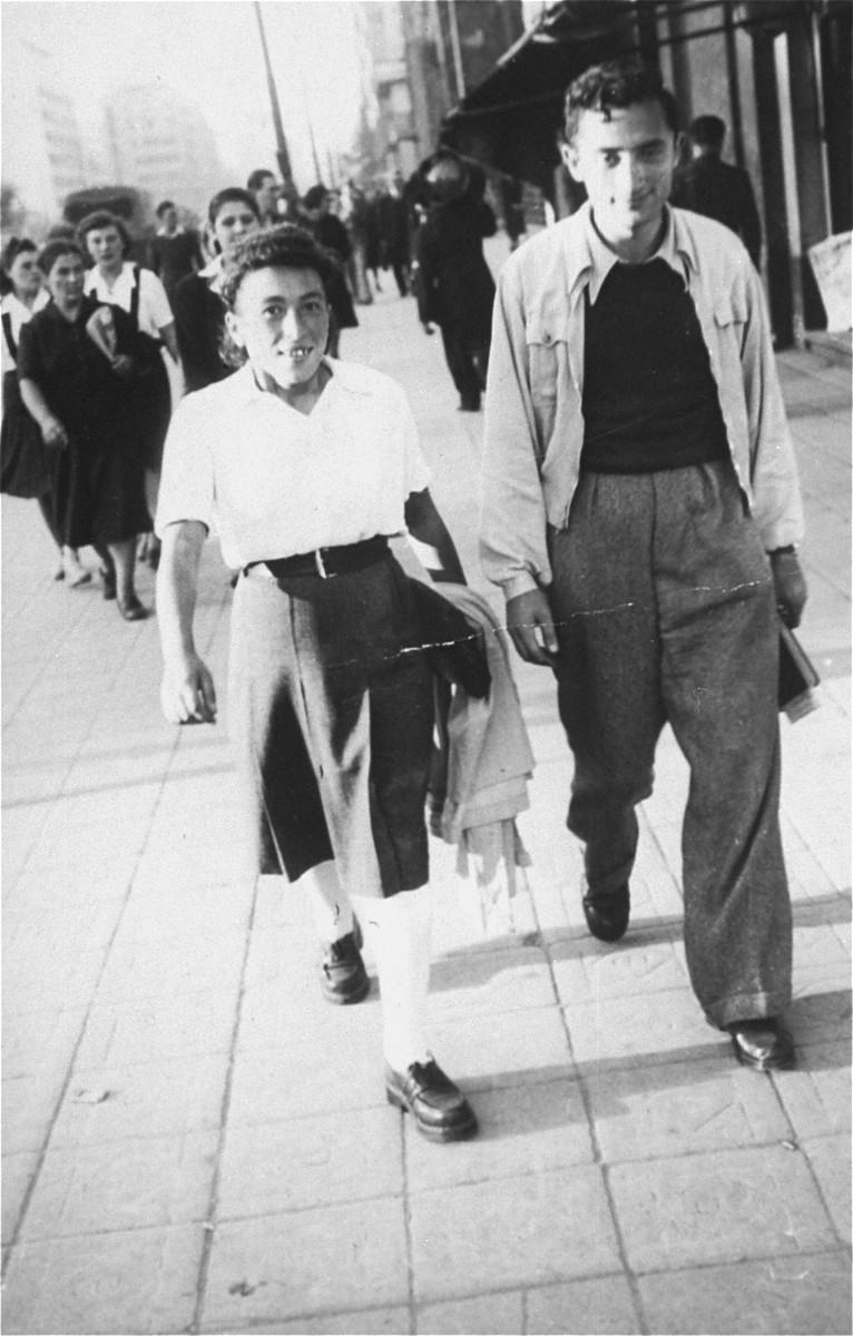 Pola Brandys and Avram Zilbersztajn walk down a commercial street in Bucharest.