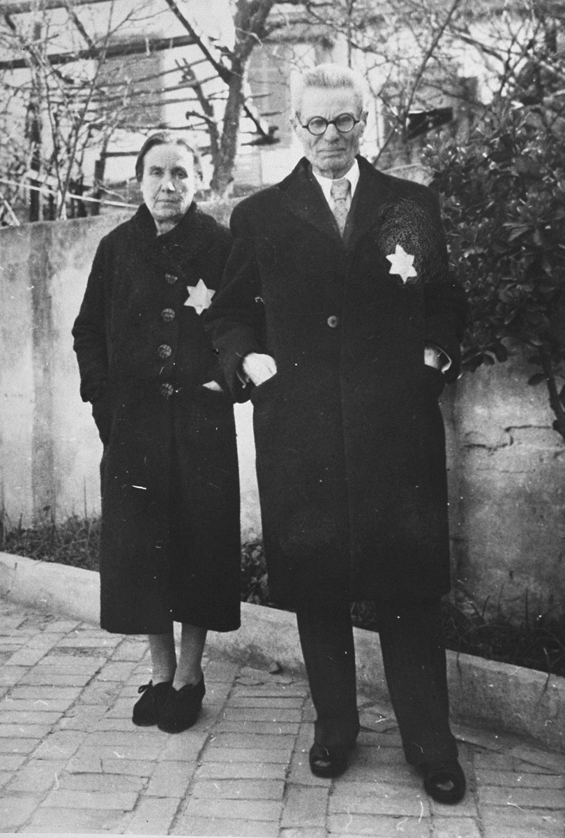 A Jewish couple wearing the yellow star poses on a street in Salonika.  Pictured are Rachel and Joseph Chasid, the parents of Margo (Chasid) Melech.