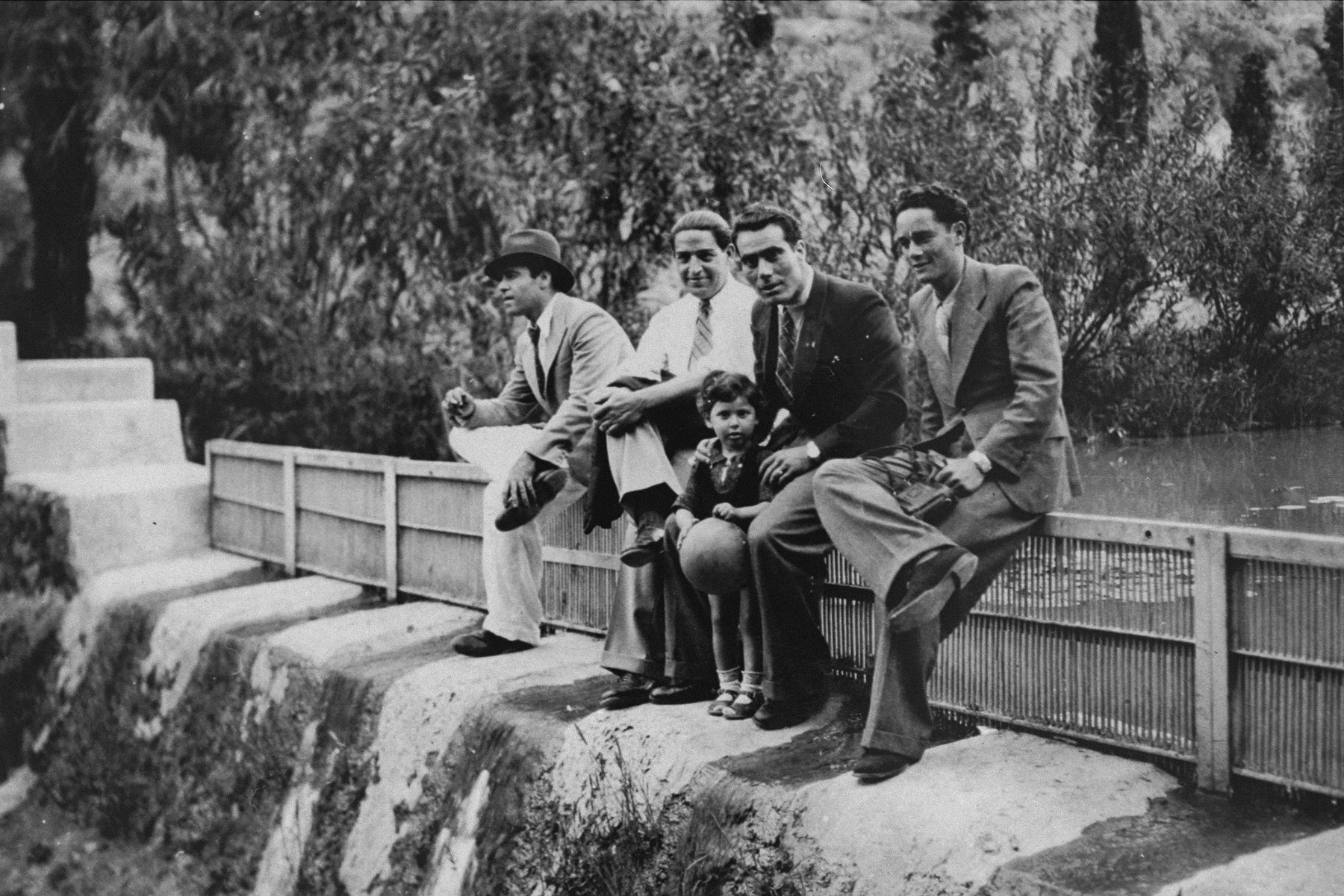 Joseph Levi, Yosef Alcana, and two other young men sit on a fence with a young child in a park.    Yosef and Joseph were both deported to Auschwitz.  Alcana perished, but Levi, a champion boxer, survived and emigrated to Israel.