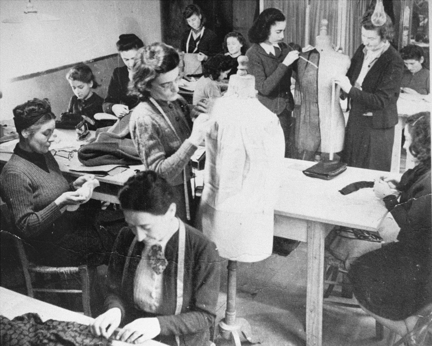 Women learn dressmaking at an ORT vocational school.    Pictured seated in the upper right hand corner is  Hermine Katz