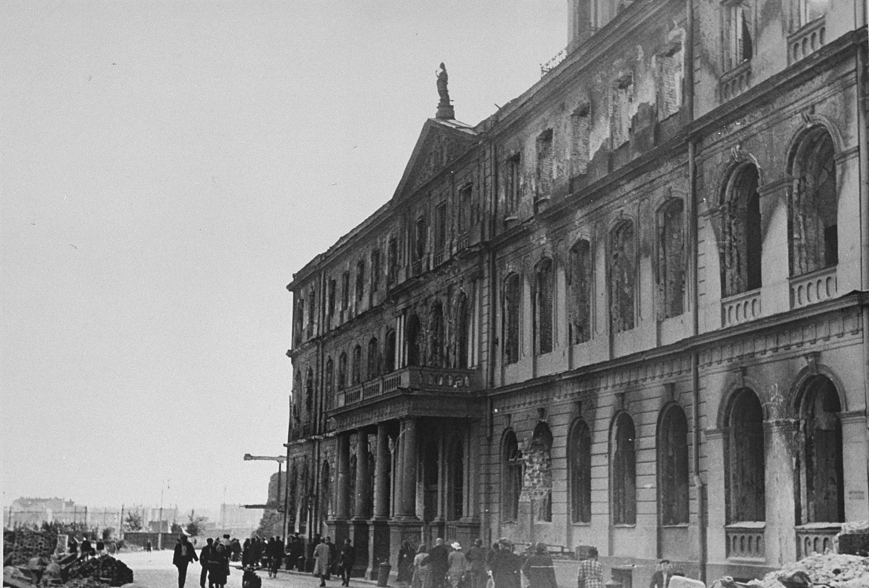 Latvian civilians walk past the Riga city hall, which was damaged in a German air raid.