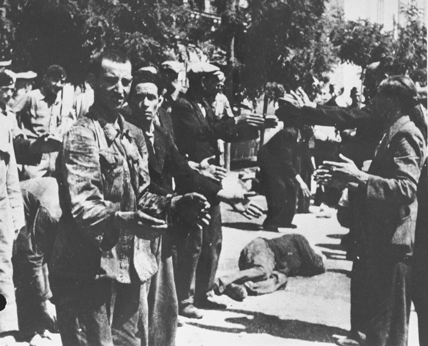 German soldiers force Jewish men to perform calisthenics on Eleftheria (Freedom) Square in Salonika.  The man in the background has collapsed from exhaustion.