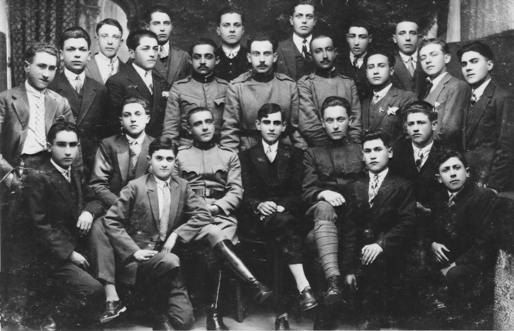 Group portrait of young Macedonian Jewish men, many of whom are wearing military uniform.