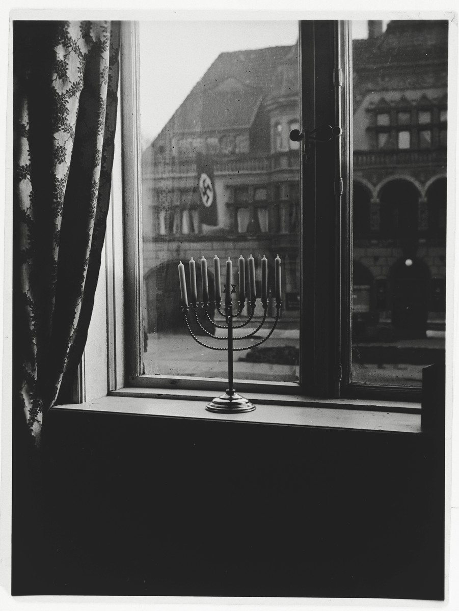 A Hanukkah menorah rests on the sill of an apartment window in Kiel.    The window looks out on the town hall, in front of which a Nazi banner hangs.  The menorah belonged to Rabbi Akiva Posner, the rabbi of Kiel.