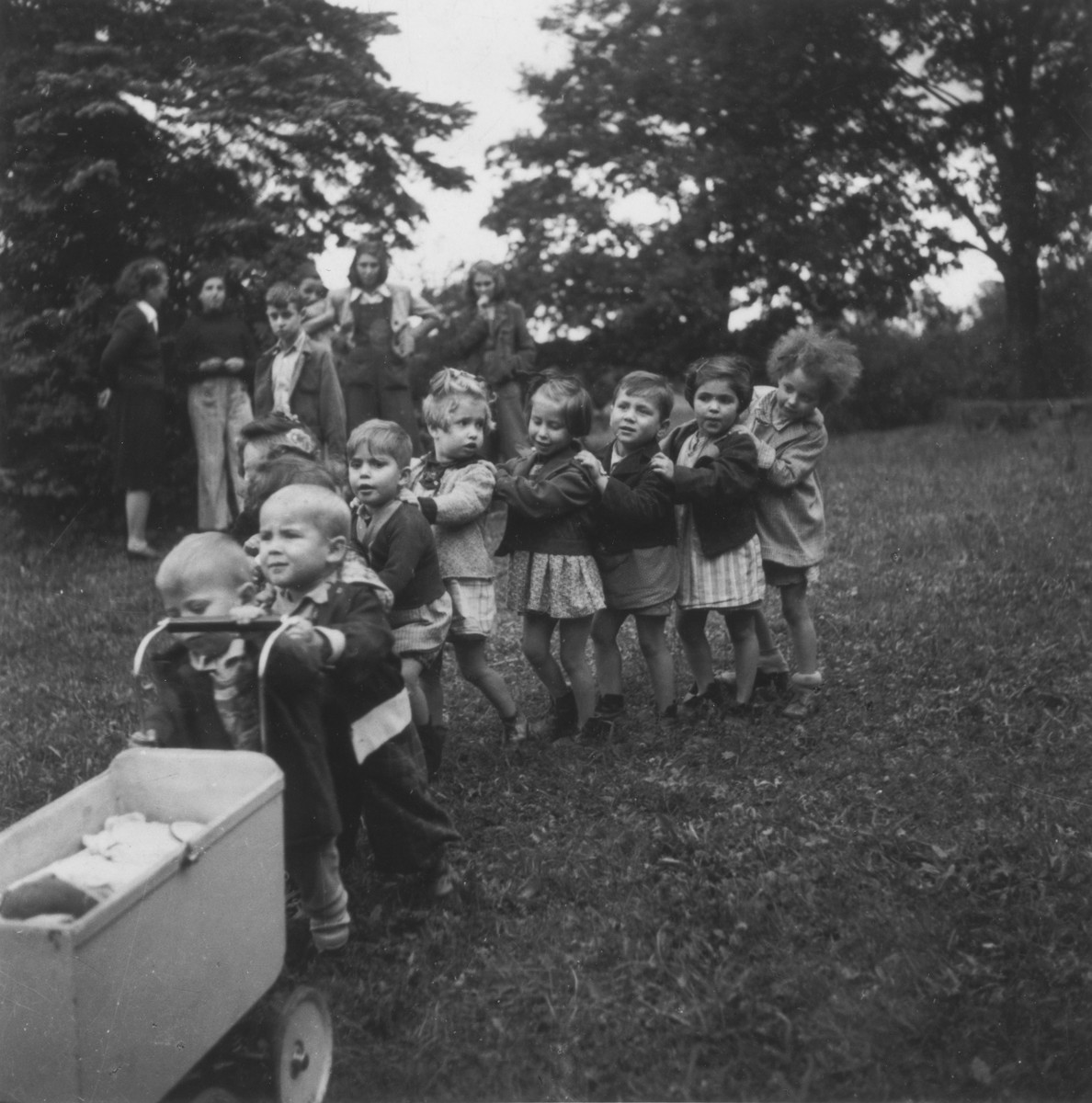 "Young DP children march in line behind a toy baby carriage in one of ""The Castles"" children's homes established by Premysl Pitter and Olga Fierzova.  The Czech inscription reads: ""Our first children out of Terezin in the Olesovice home."""