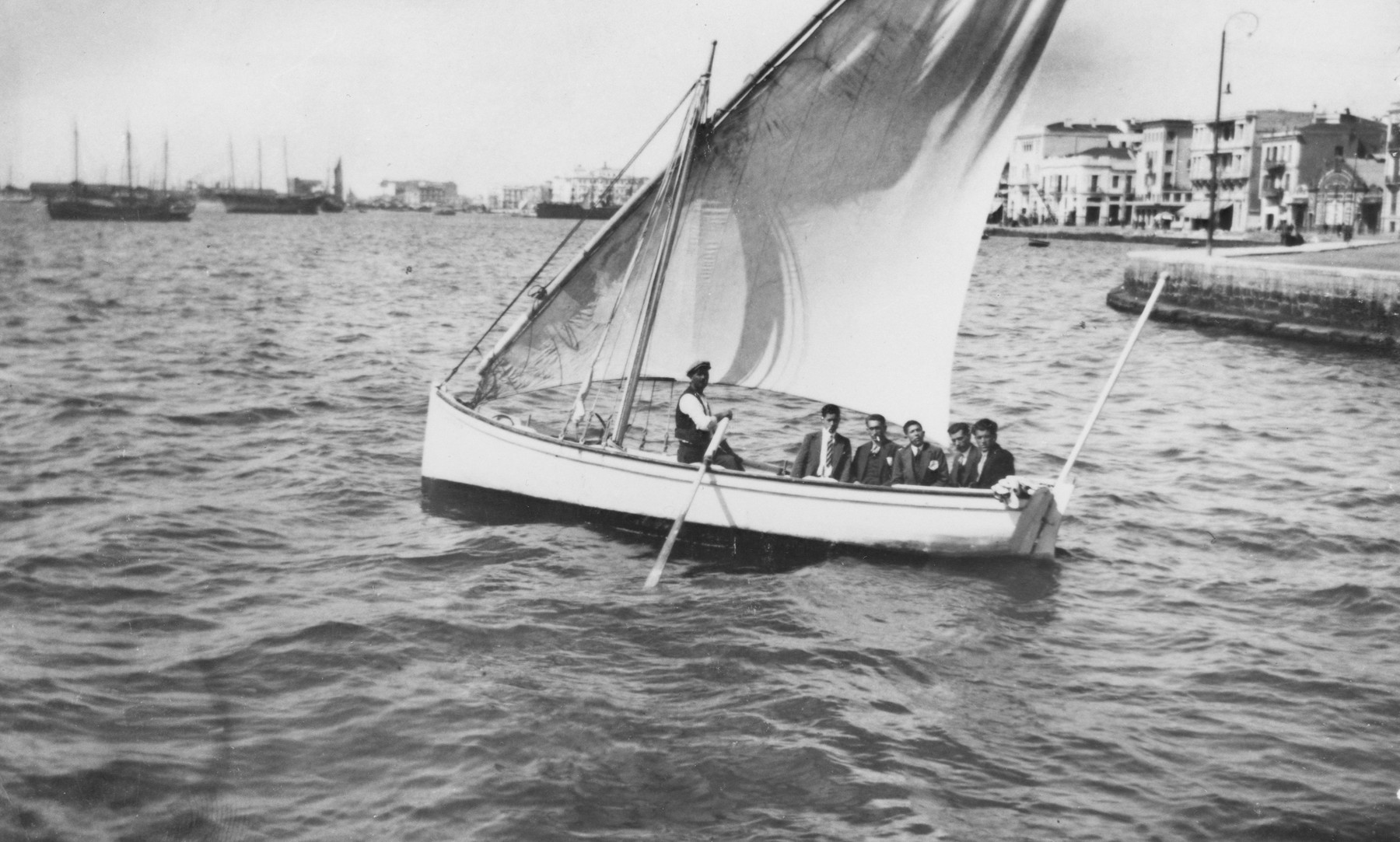 A group of  young Jewish men go for a sail in the harbor of Salonika.