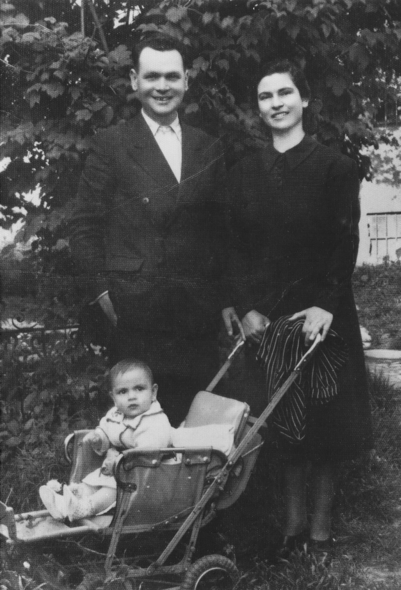 Portrait of a young Jewish couple pushing their infant in a baby carriage.