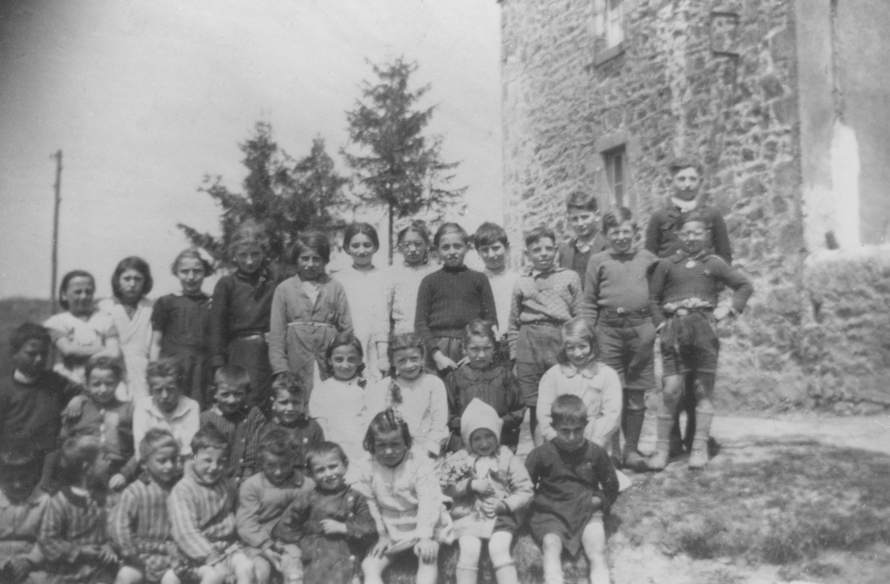 Class picture of a French school in Le Chambon where Micheline and Annette Federman and their cousins were hidden.  Micheline Federman is pictured in the front row, second from the right.  Her cousin Helene is pictured in the second row on the far right.  Annette is pictured standing second from the left, and another cousin Rene is standing fourth from the right.