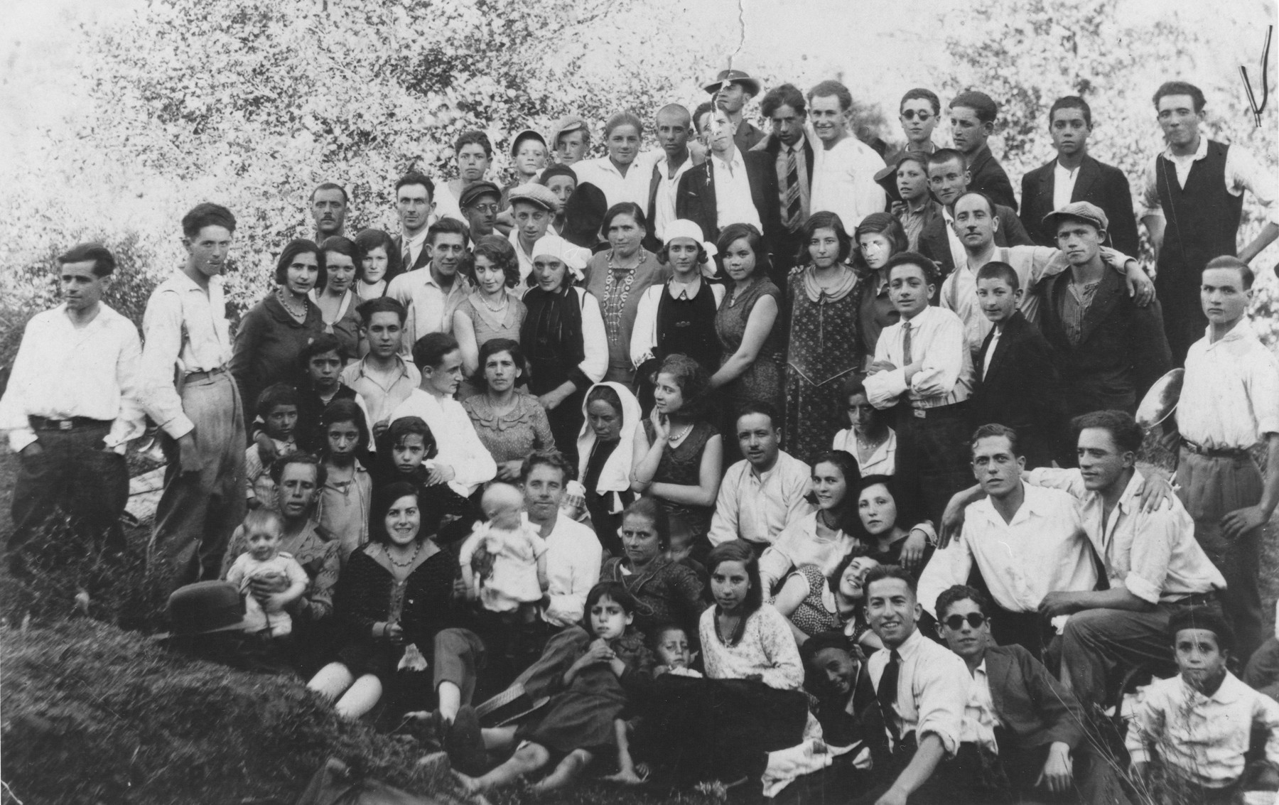 A large group of  young Jewish men and women pose outdoors near a woods in Bitola.