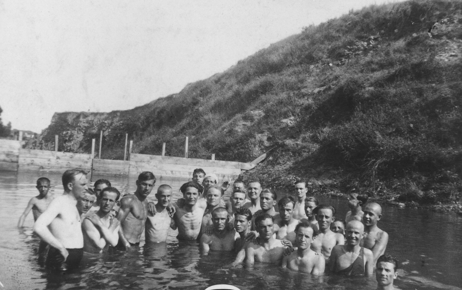 A group of Jewish young men pose together while swimming in a lake.