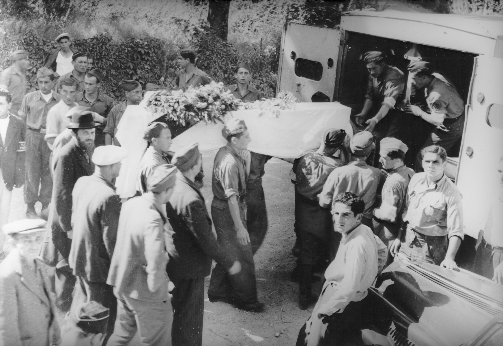 Jewish policemen hoist a coffin onto a truck during the funeral for another Jewish policeman in the Feldafing DP camp.