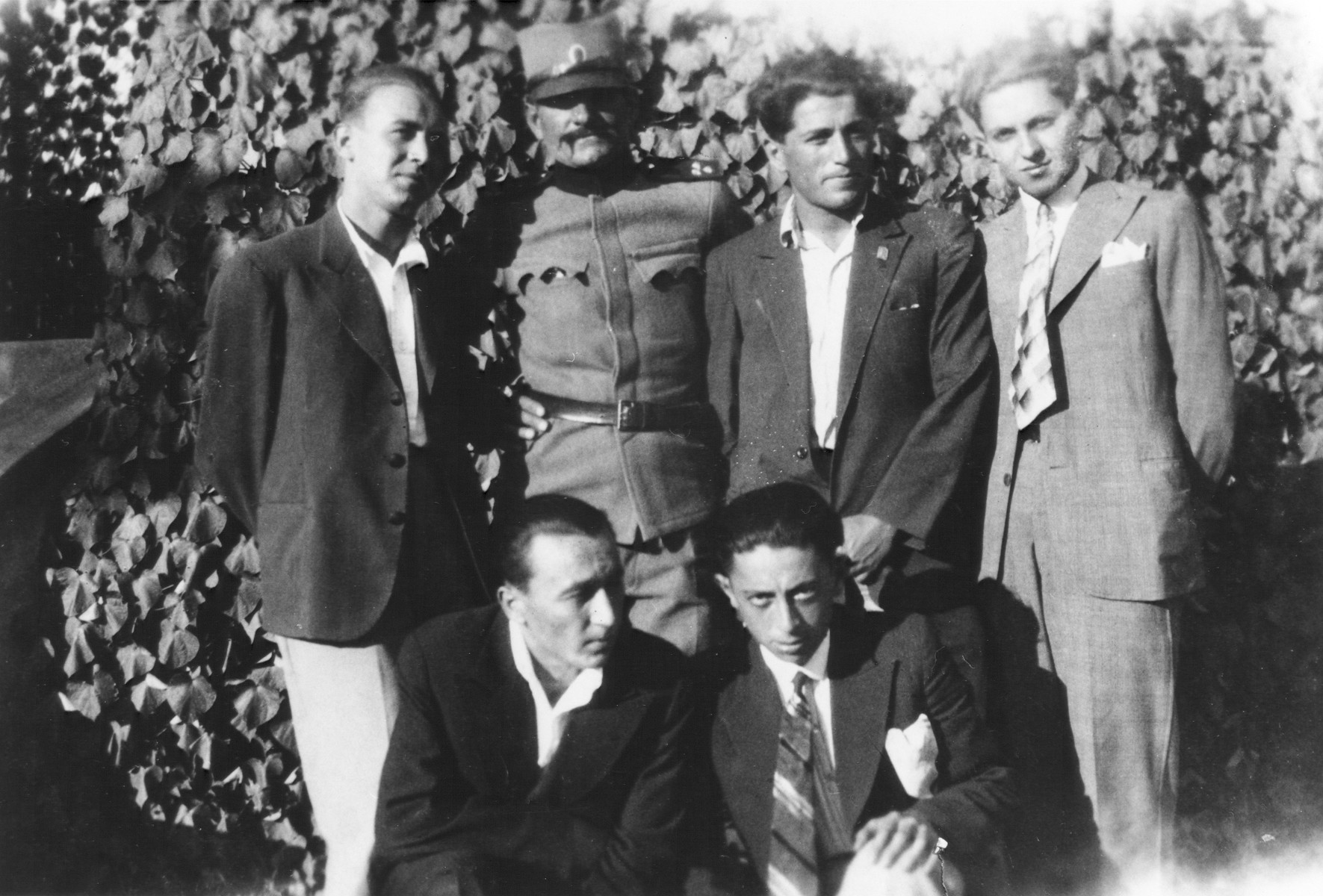 Group portrait of six Macedonian Jewish men, one of whom is wearing military uniform.