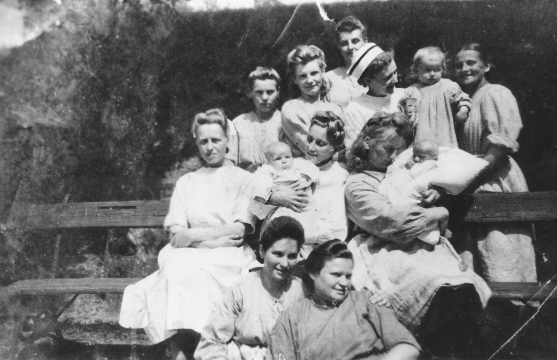 Nurses at an orphanage pose with some of the babies including a Jewish child in hiding.  Among the children is Wanda Szymeczko.