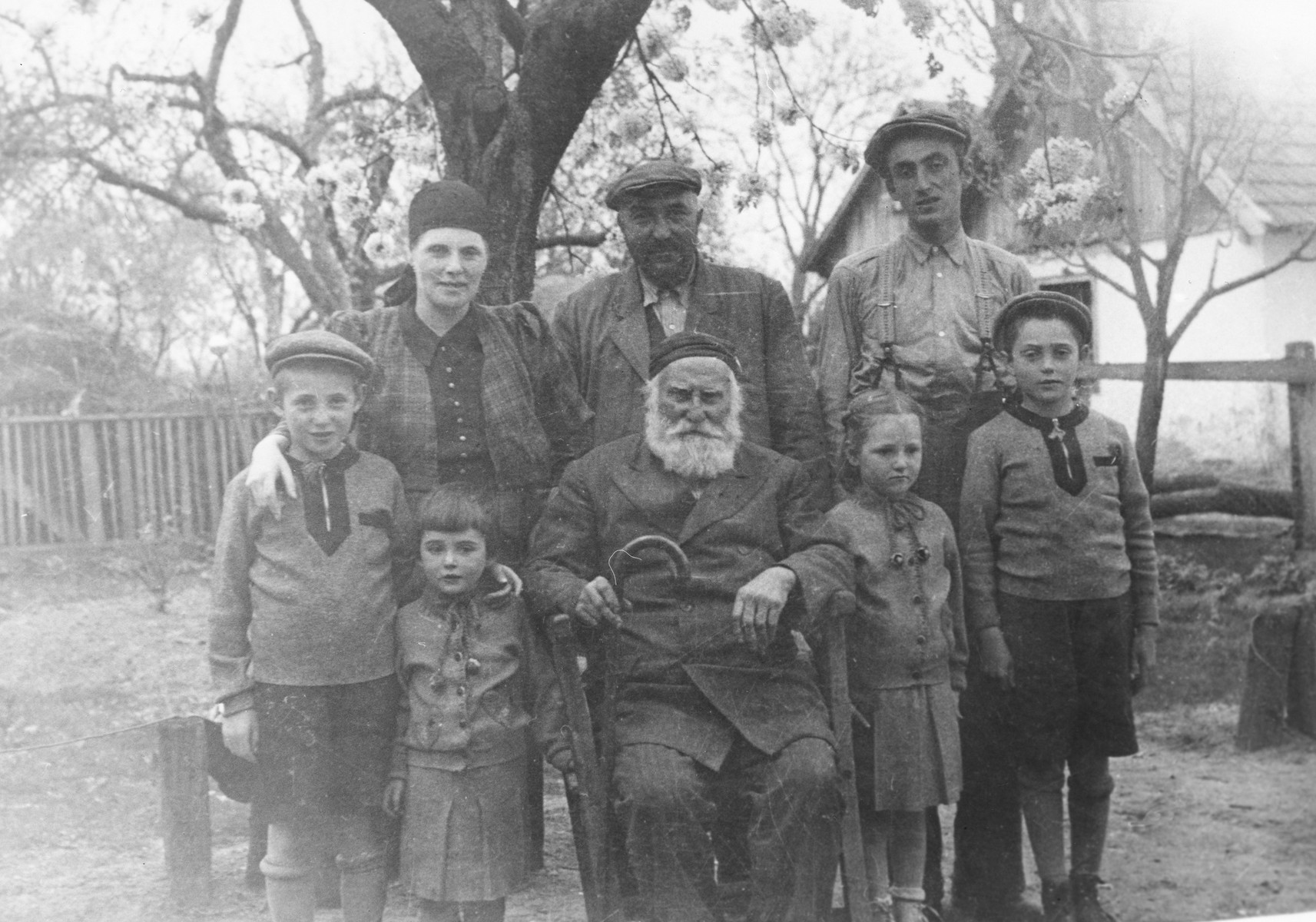 The Farkas family poses in the backyard for a family portrait taken by a visiting uncle from America.  Pictured front row (left to right): Zoltan Farkas, Judit Farkas, Yaakov Koppel Farkas, Eva Farkas and Erwin Farkas.  Back row: Frieda Frankel, Jeno Farkas and Sholom.