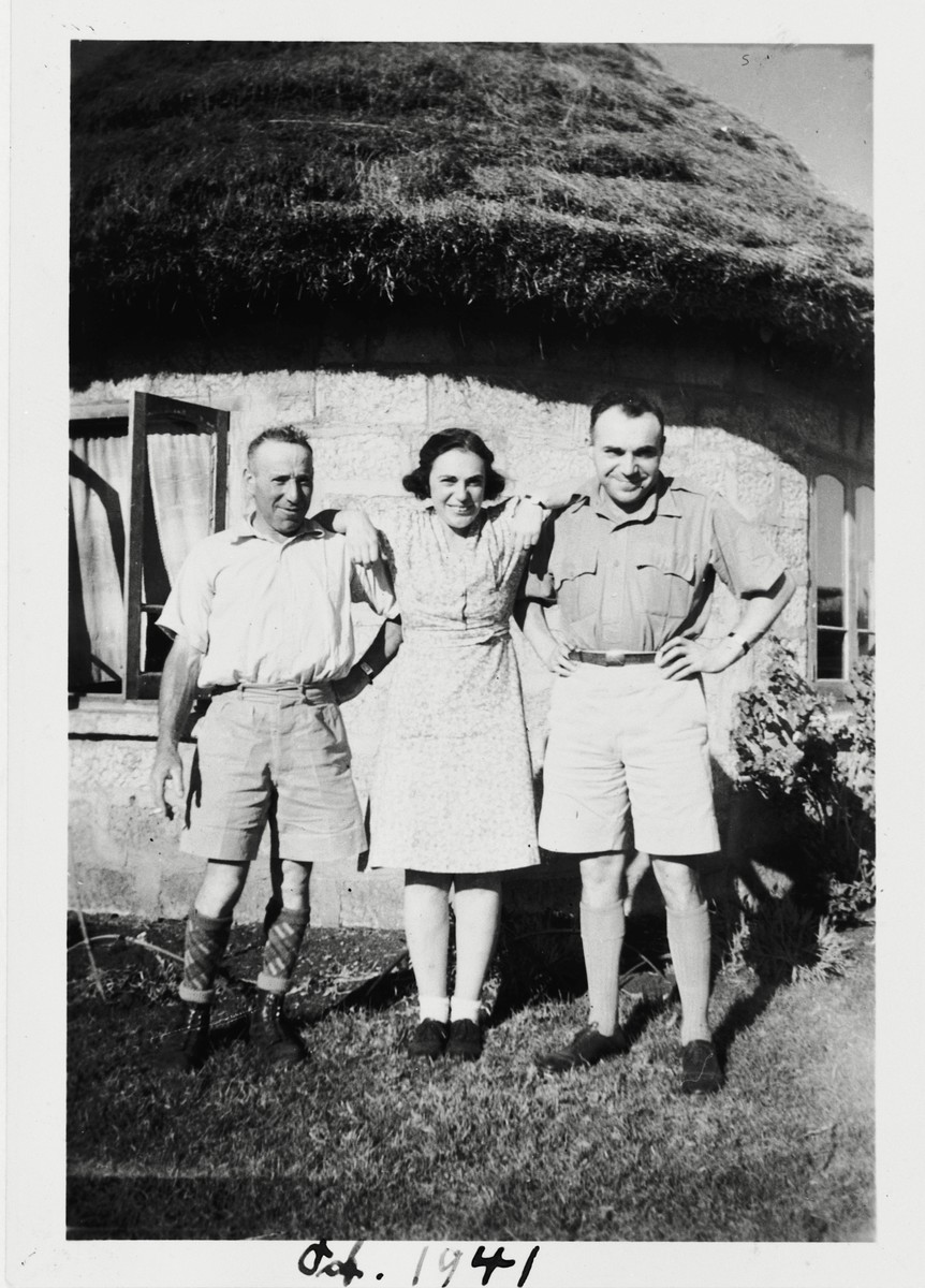 Three German Jewish refugees pose outside a thatched-roof dwelling in Kenya, where they found refuge during World War II.  Pictured are Herman Strauss with his sister, Relly Strauss Marx, and her husband, Moritz Marx.  Herman Strauss obtained 21 visas to bring his relatives to Kenya.