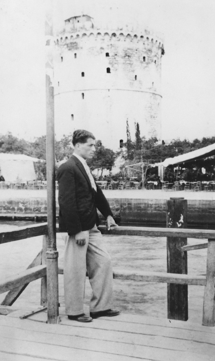 A young Macedonian Jewish man stands on a board walk opposite a castle.