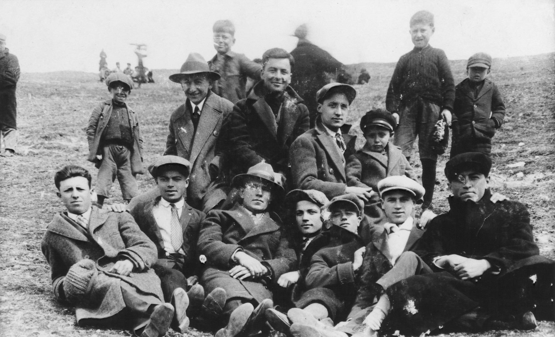 A group of  young Jewish men and boys relax outdoors  in an open field near Bitola.