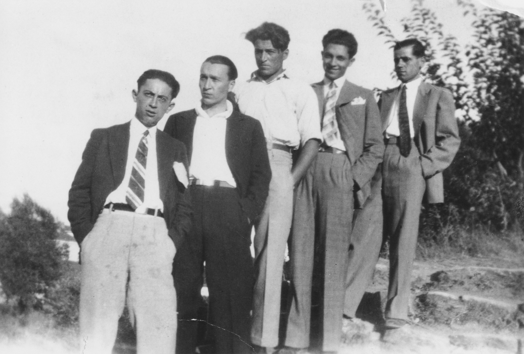 Five Jewish young men pose outdoors standing in a line.