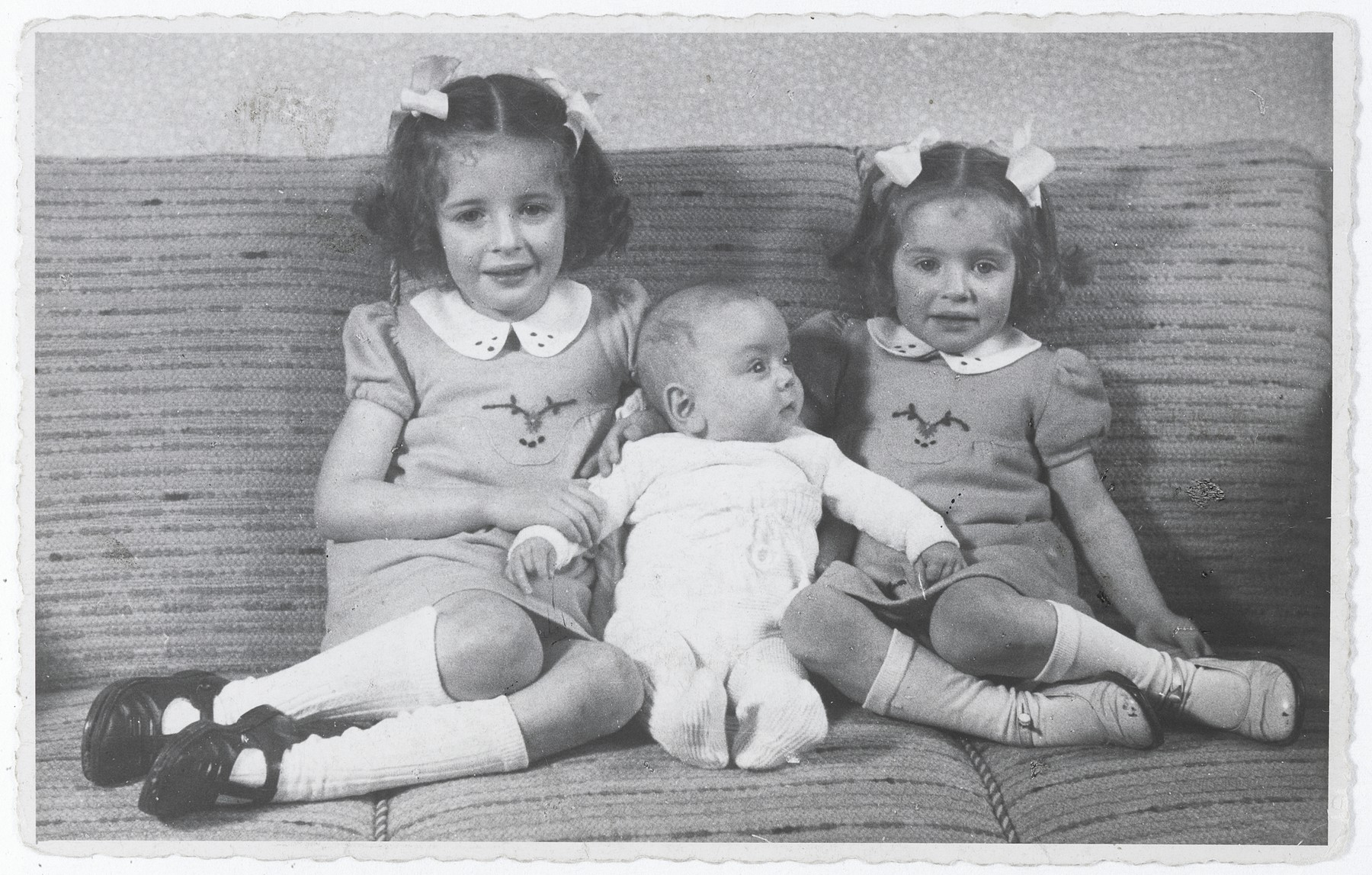 Three Jewish siblings pose on a sofa in their home in The Hague.  Pictured from left to right are Eva, Alfred and Leana Münzer.  The two girls later perished in Auschwitz.