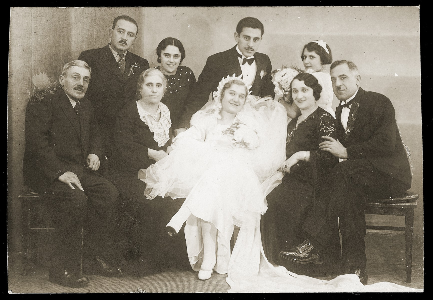 Group portrait of family members at the wedding of Mosa (Moshe) Mandil and Gabriela (Ela) Konfino in Belgrade.    Pictured are Mosa Mandil and Gabriela Konfino, the groom and bride, David and Regina Mandil, the groom's parents (seated on the left); Gavra and Elisabeth Konfino, the bride's parents (seated on the right); Streja Mandil, the groom's sister, and her husband (standing on the left); and Gizela Konfino, the bride's sister (standing on the right).
