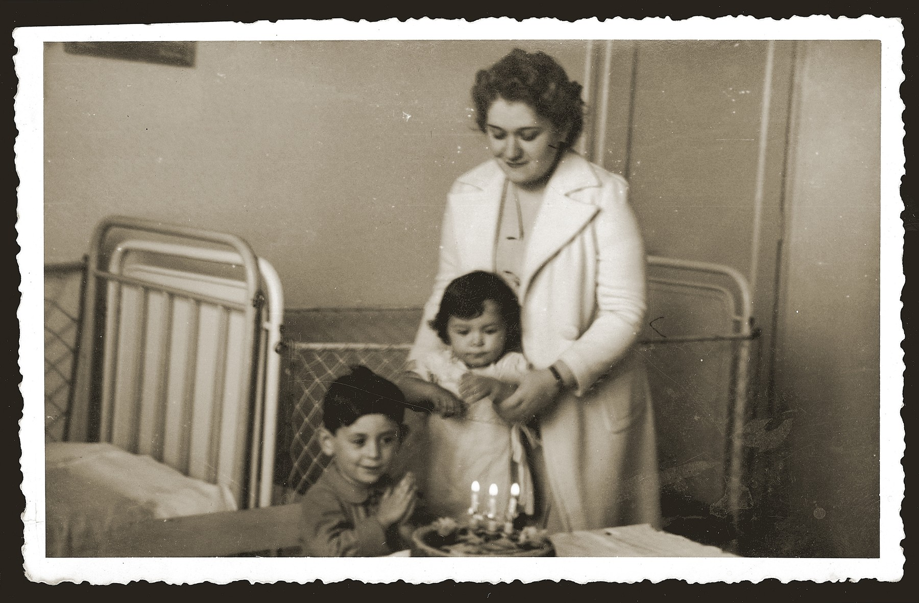 Gavra Mandil celebrates his third birthday with his mother and sister.