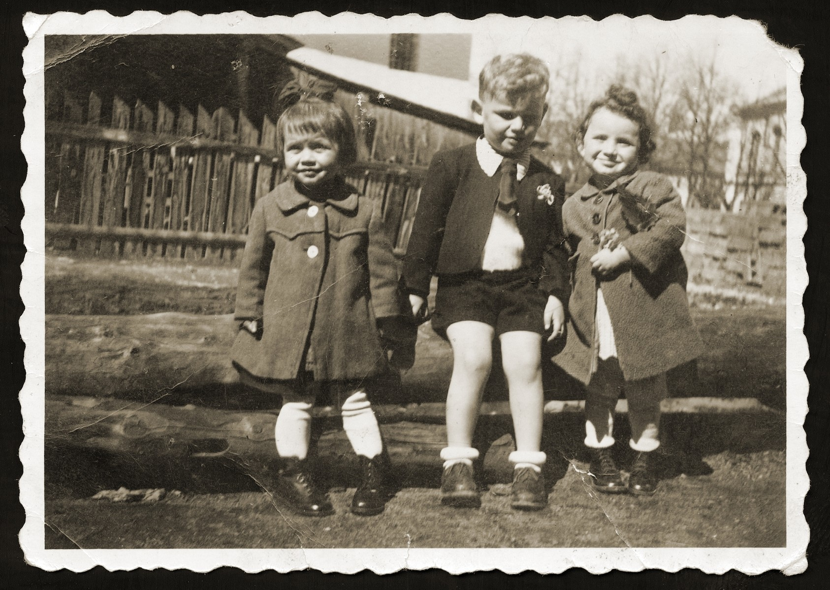 Three young children pose outside in a yard in Nemecka Lupka shortly before two of them were deported to Theresienstadt.  Pictured from right to left are Denise Elbert, Egon Gal and their non-Jewish friend, Viola.