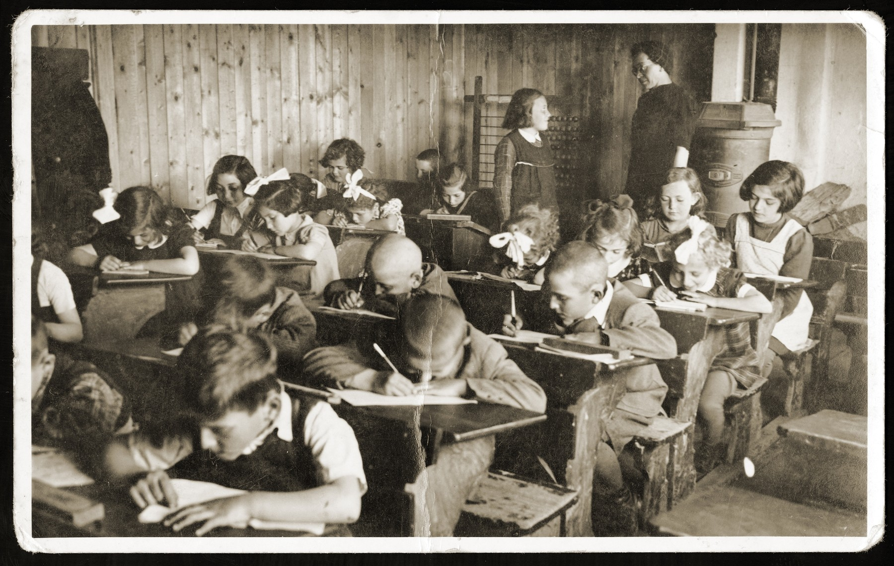 Children do their school work in a classroom in the Novaky labor camp.  Among those pictured is Richard Kohn (in the second horizontal row, first on the right).