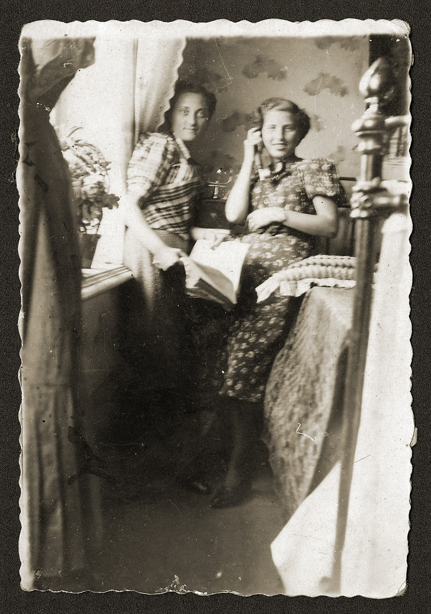 Two young Jewish women, one of whom is talking on the phone, sit in a private home in Opatow, Poland.  Pictured is Cyla (Fefer) Sztajnman (right) with her sister-in-law, Fela Sztajnman (left) in Fela's home.