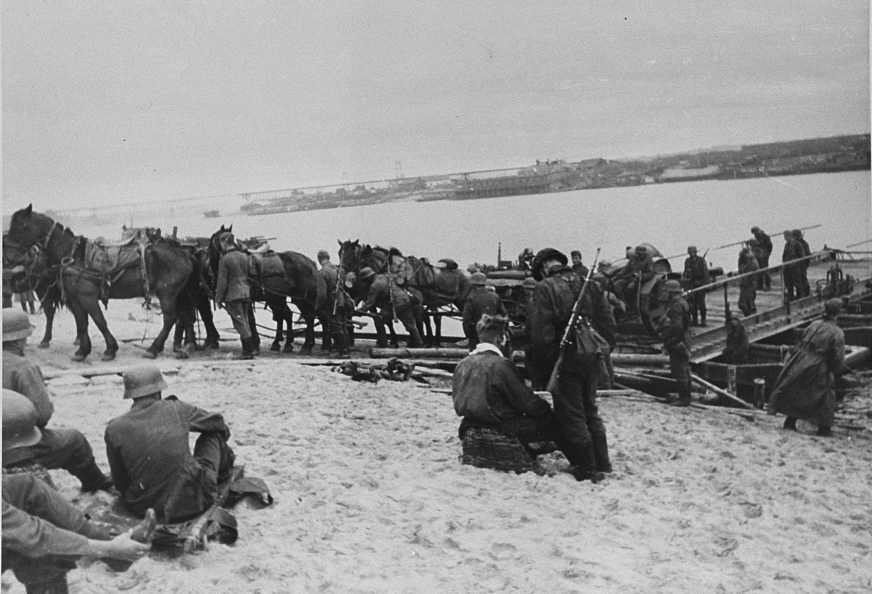 "SS troops with the ""Wiking"" Division unload artillery brought across a river by barge."