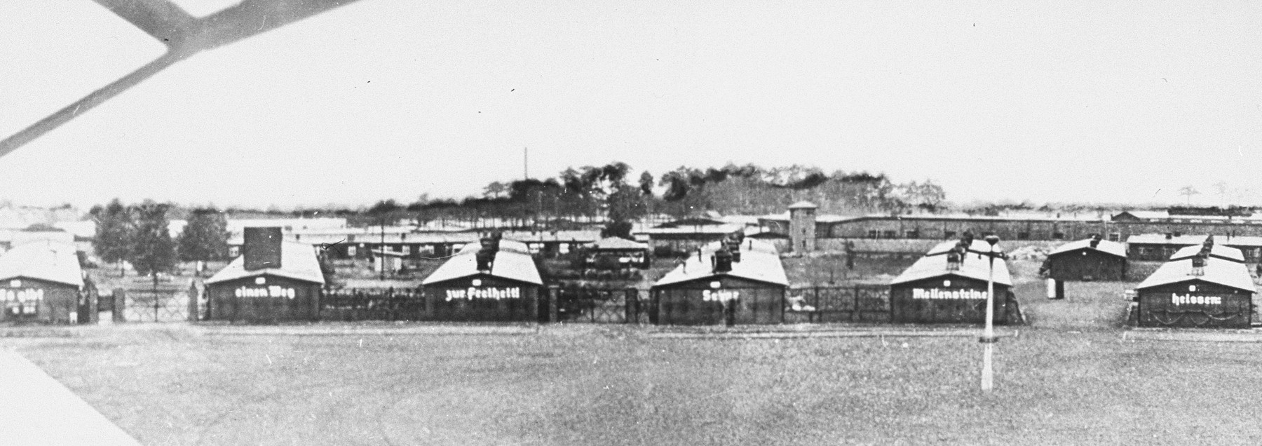 View of the prisoners' barracks in Sachsenhausen, with Nazi slogans painted on the front. [Oversized print, one of three, making up a panorama]