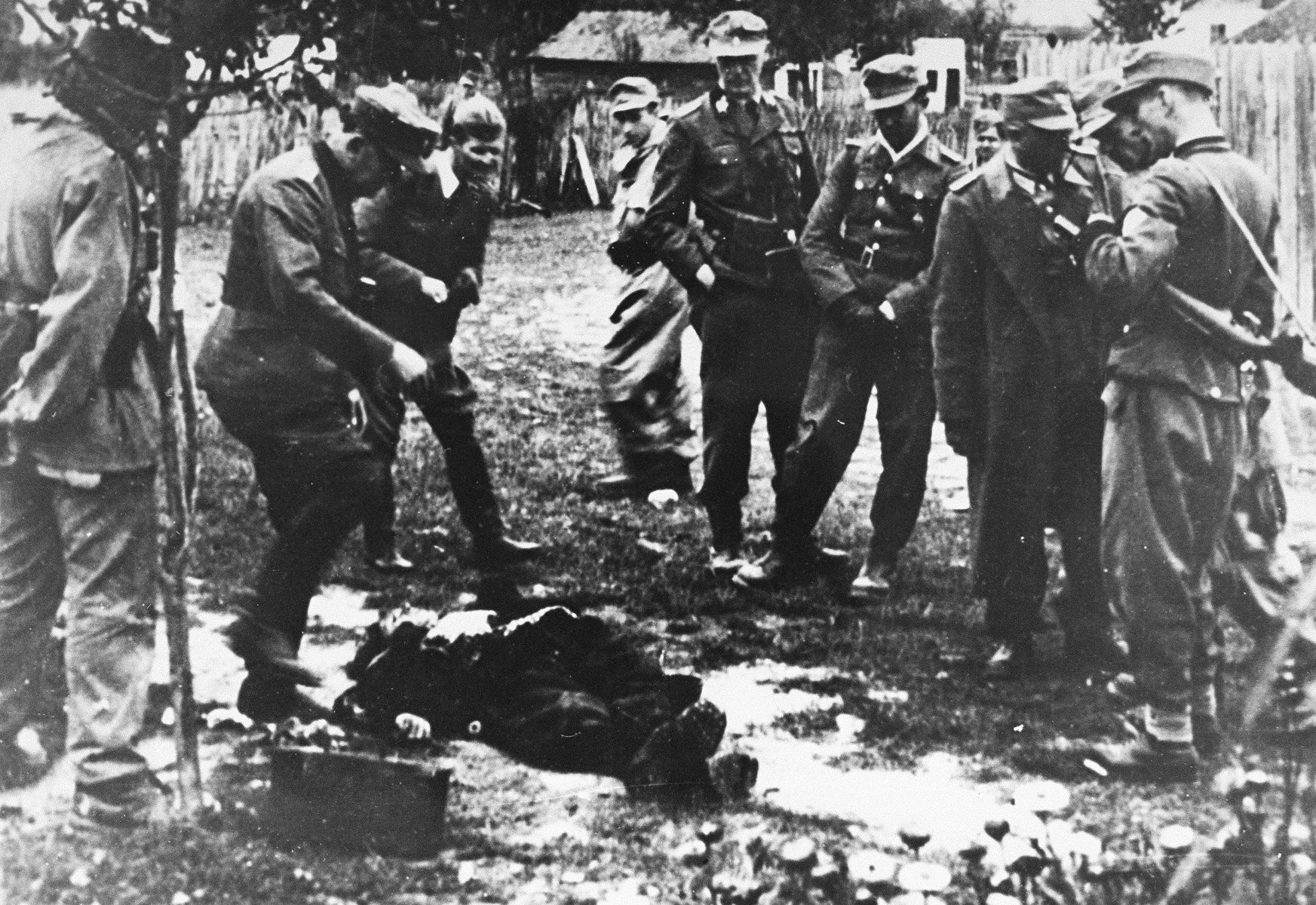 """A soldier with a unit of German mountain troops kicks a man to death during the """"cleansing"""" of the Macva region in September 1941.  The man third from left is a Ustasa officer."""