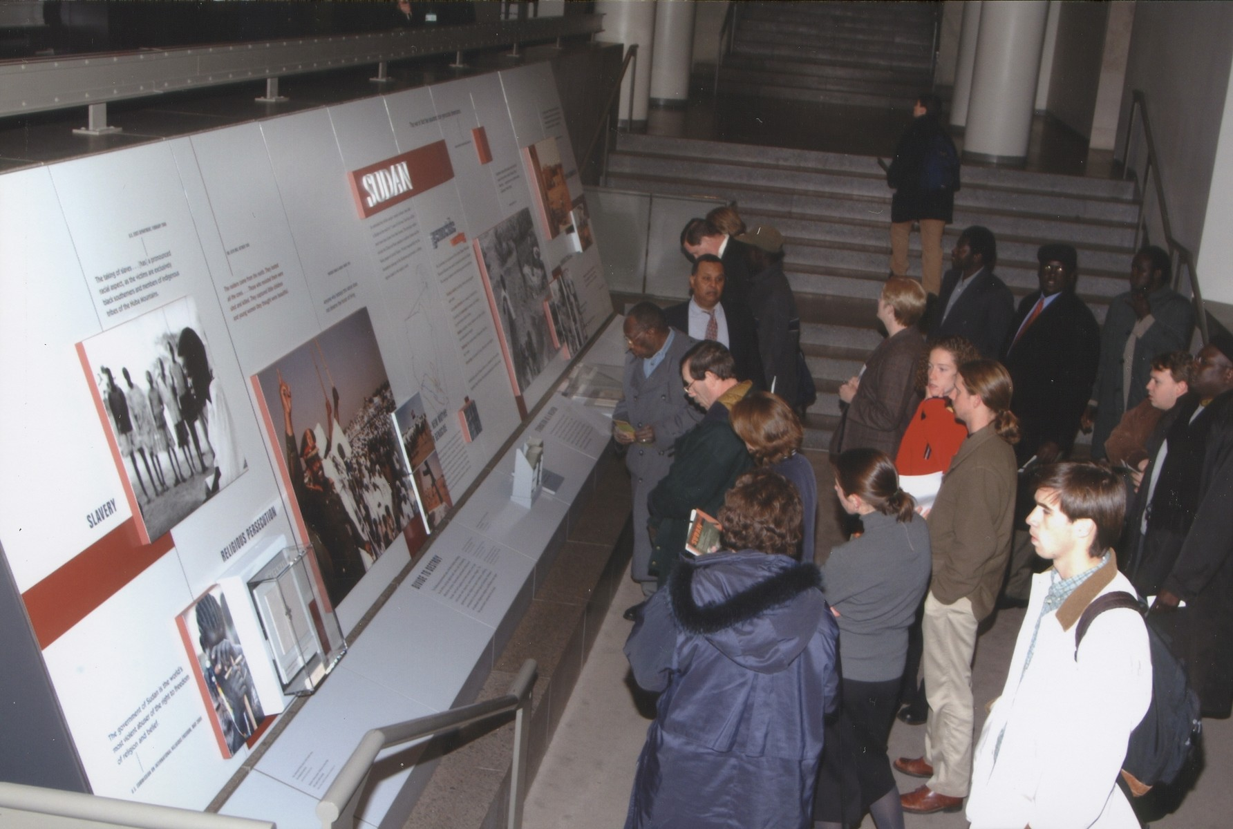"Visitors viewing ""Sudan,"" a special exhibition sponsored by the Committee on Conscience, on display outside the Meyerhoff Theater at the U.S. Holocaust Memorial Museum."