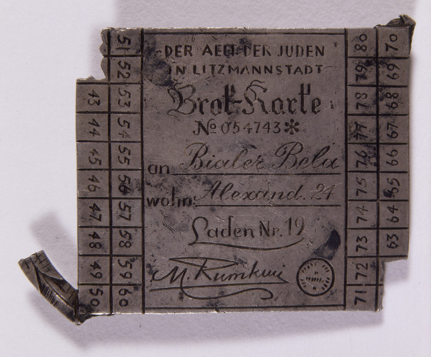 Metal brooch designed in imitation of the ration card issued to Bela Bialer in the Lodz ghetto.  The pin mimics the signature of Chaim Rumkowski, chairman of the Lodz ghetto Judenrat.  The pin may have been created by Chaim Klieger, a Lodz ghetto resident.
