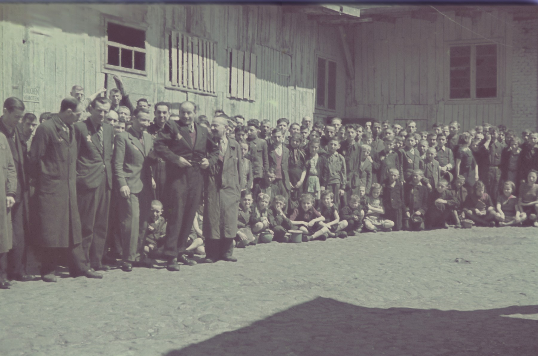 "Group portrait of personnel, including many children, of the furniture factory in the Lodz ghetto.  Original German caption: ""Getto Litzmannschaft, Gefolgschaft der  Moebelfabrik"" (personnel of the furniture factory), #176."