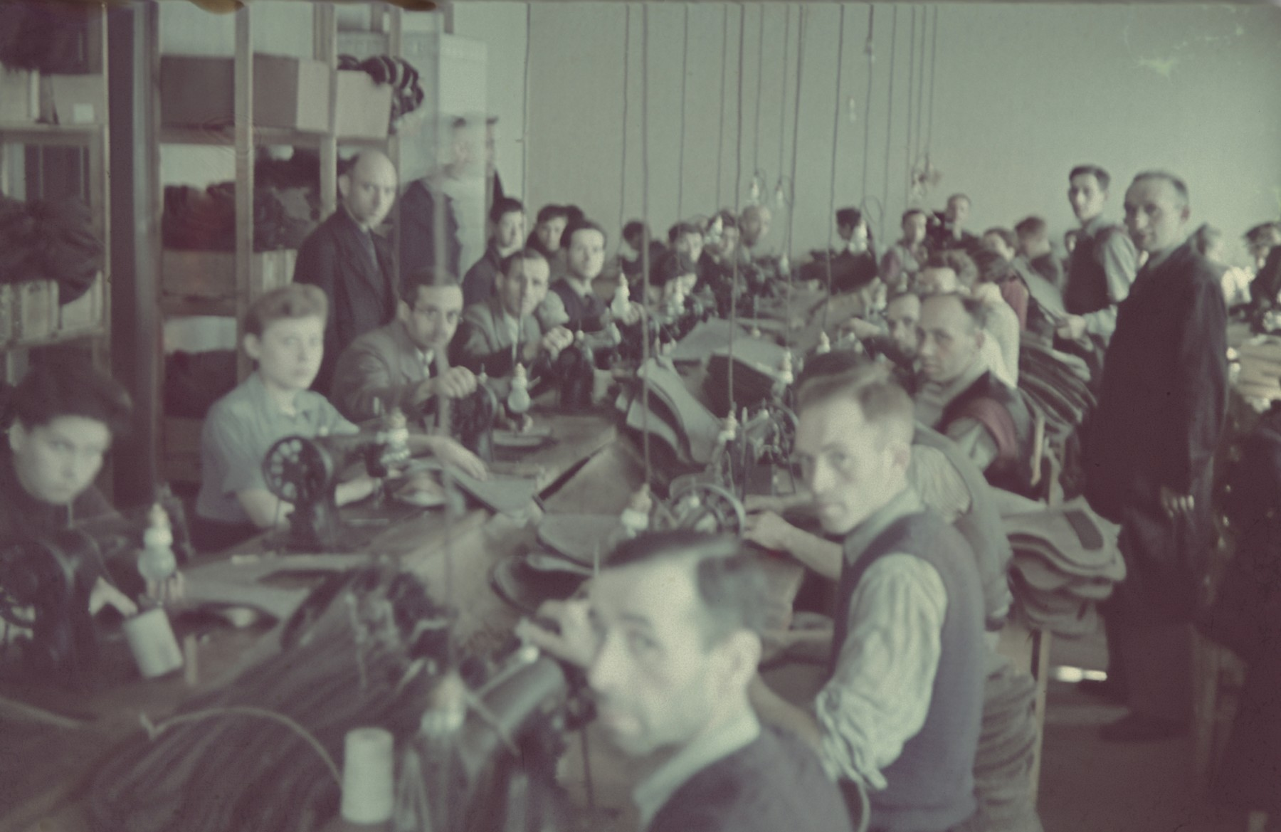 """Workers operate sewing machines in the saddle-making workshop of the Lodz ghetto.  Original German caption: """"Litzmannstadt-Getto, Sattlerei"""" (saddlery)."""