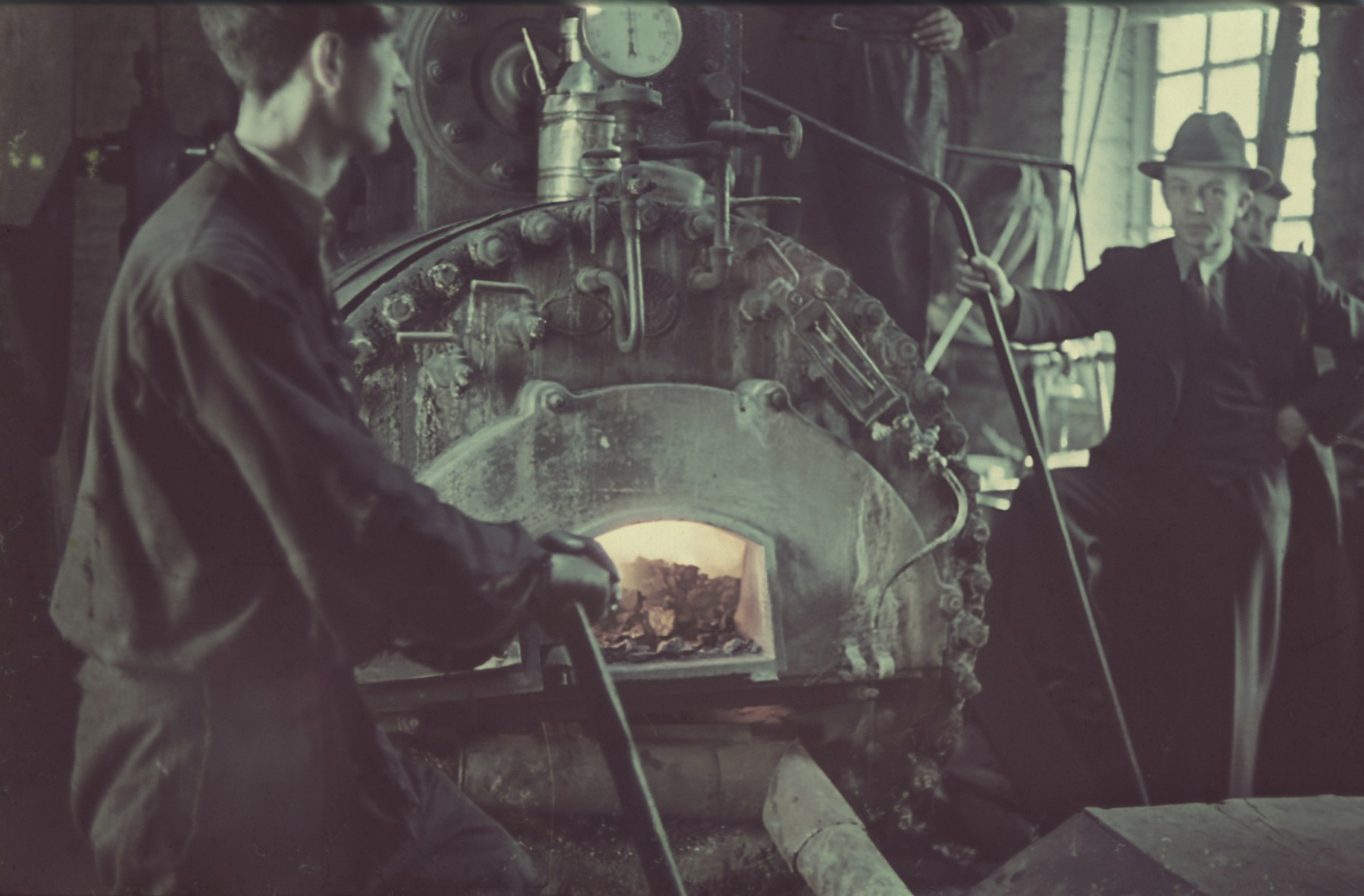 "A worker stokes the furnace of a furniture factory in the Lodz ghetto.  Original German caption: Getto, Litzmannstadt, ""Heizhaus in Moebelfabrik"" (heating facility furniture factory), #214.  (Number 168 is crossed out.)"
