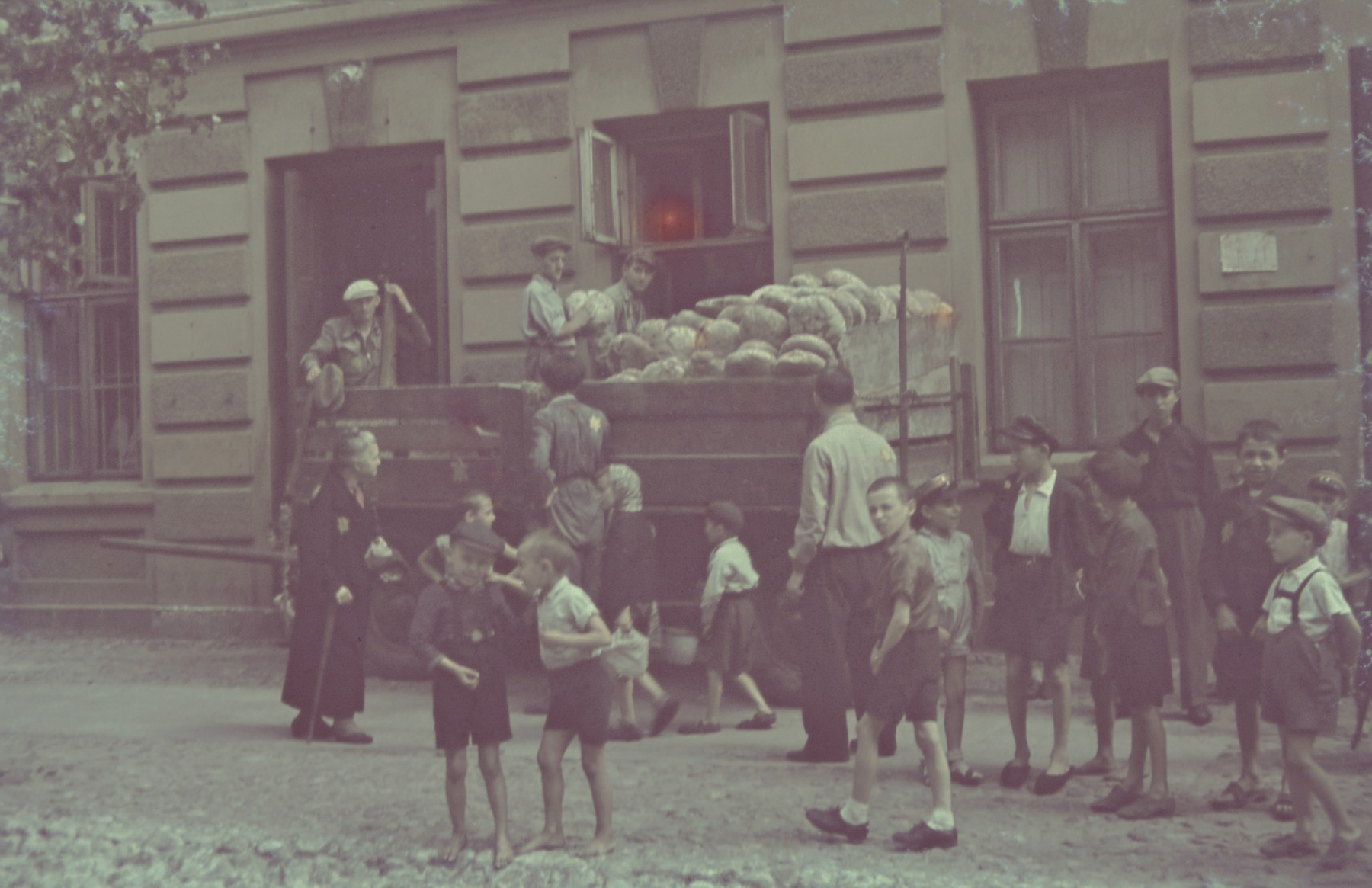"Children wait outside the bread distribution center in the Lodz ghetto.  Original German caption: ""Strassenbild"" (street scene), #147."