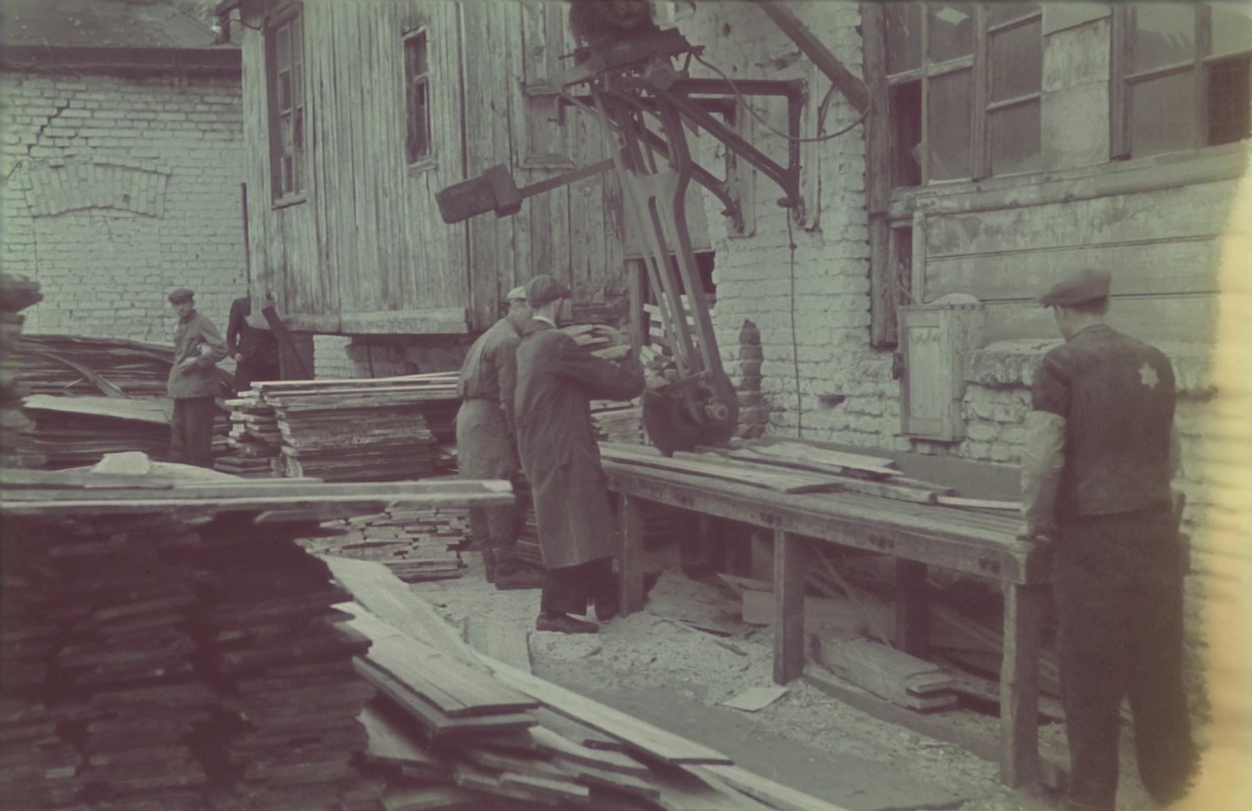 "Carpenters work in the Lodz ghetto furniture factory.  Original German caption: ""Litzmannstadt ghetto, Moebelfabrik"" (furniture factory)."