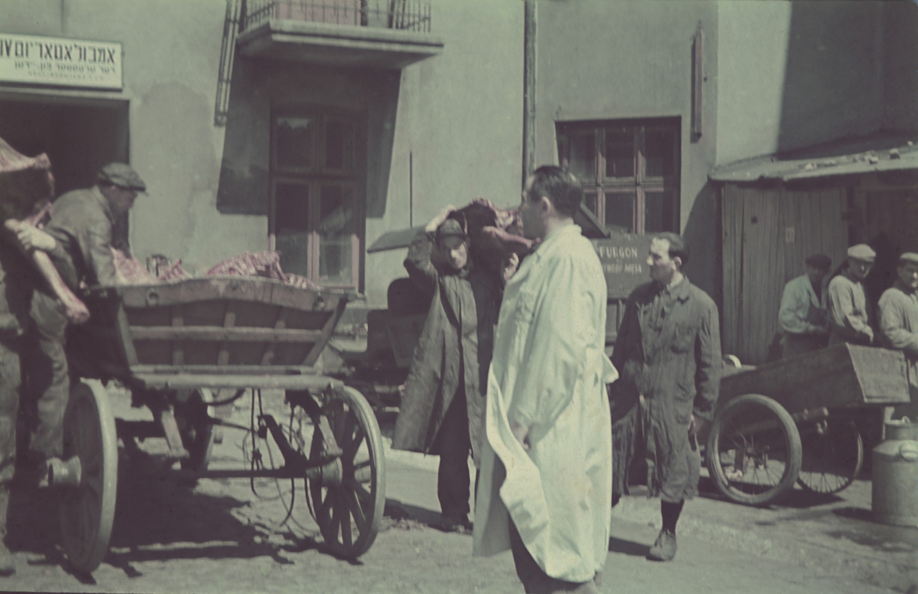 """Workers fill a cart full of meat  for distribution to the ghetto.  Original German caption: """"Getto Litzmannstadt, Fleischzentrale"""" (meat distribution center), #182.  Pictured ito the right of the man in the white coat is Avraham Ast."""