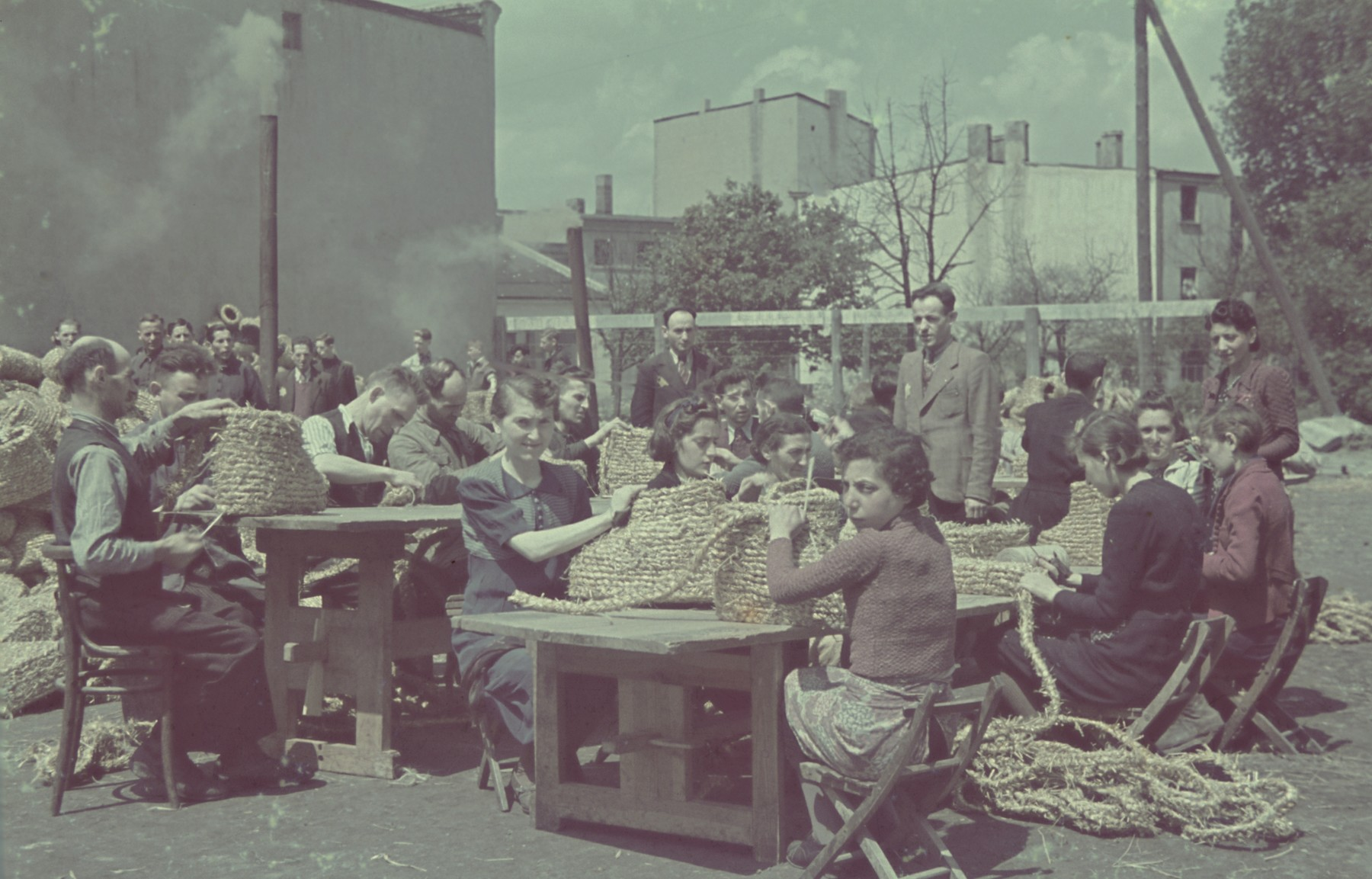 "Workers roll up coils of straw in the straw shoe factory of the Lodz ghetto.  Original German caption: ""Getto-Litzmannstadt, Strohschuhfabrik"" (straw-shoe factory), #206."