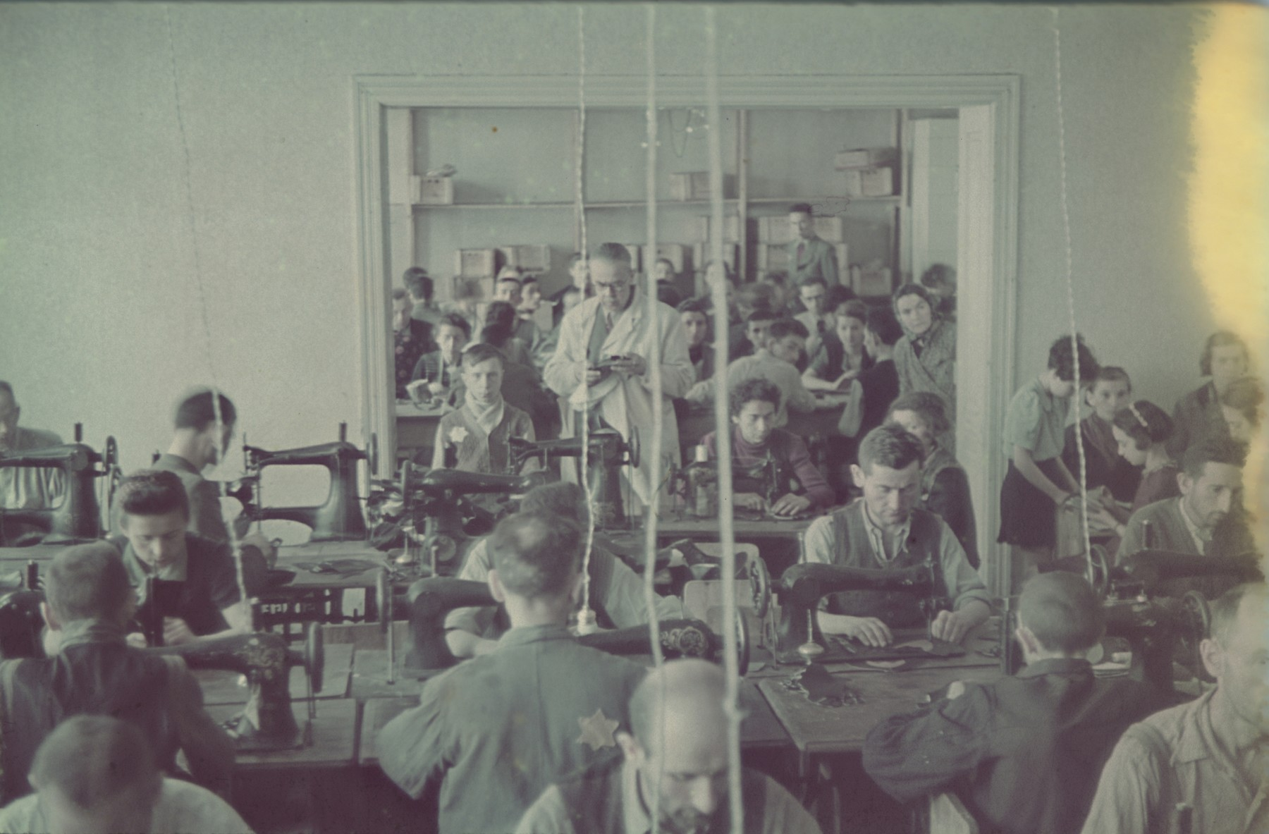 "Workers operate sewing machines in the saddle-making workshop of the Lodz ghetto.  Original German caption: ""Litzmannstadt-Getto, Sattlerei"" (saddlery)."