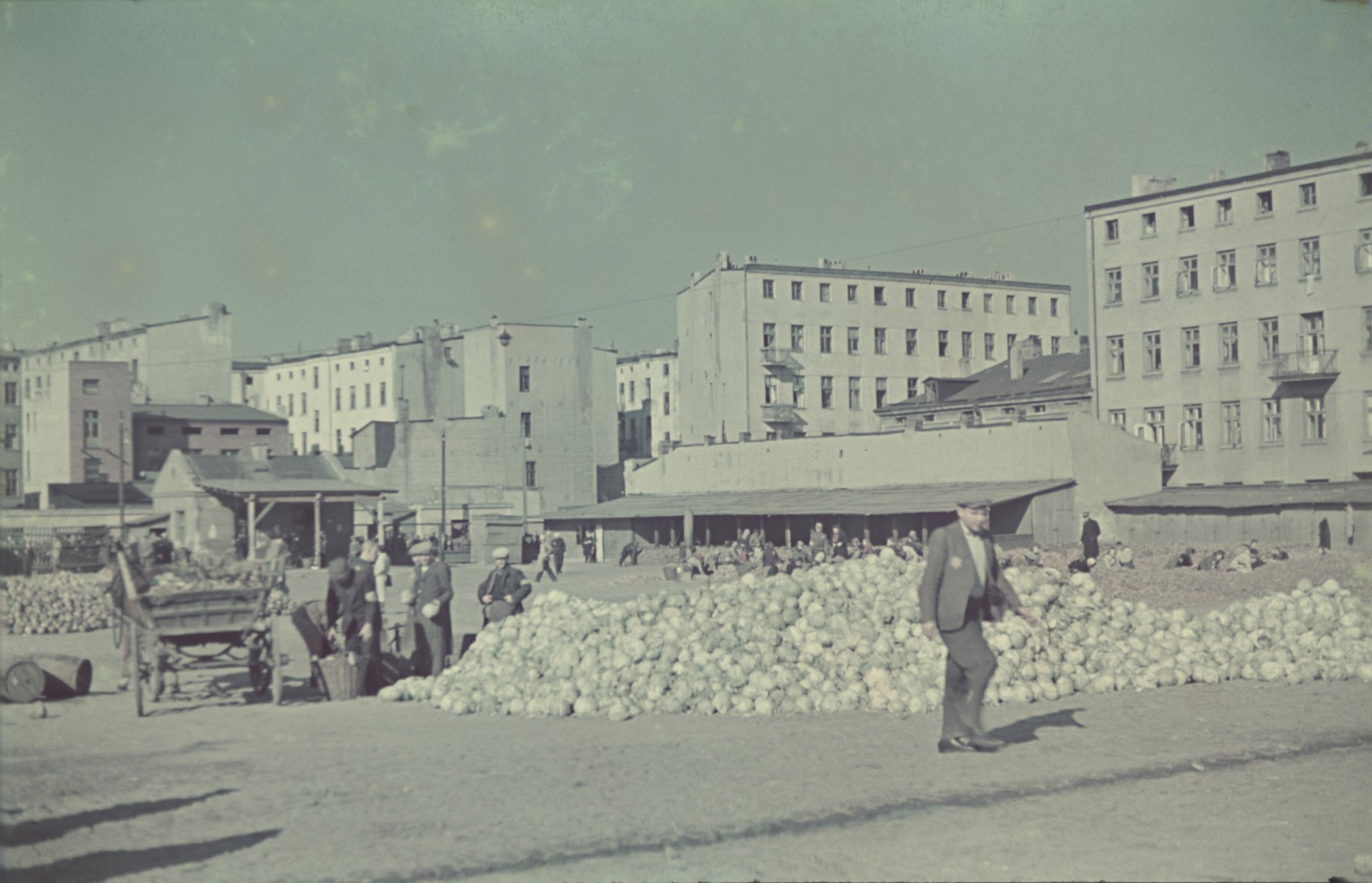 "A man walks past a past a pile of vegetables in the Lodz ghetto central square.  Original German caption: ""Lagerplatz"" (camp square), #144."