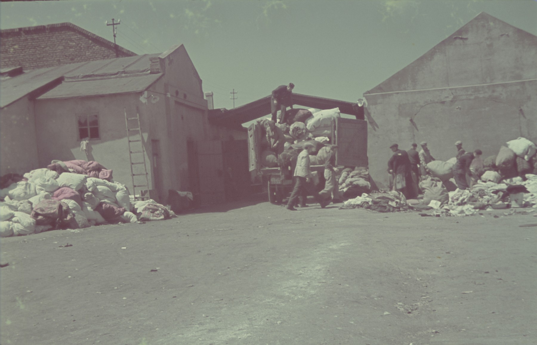 "Jews load bales of confiscated goods onto trucks in the Pabianice labor camp/storage facility.  Original German caption: ""Pabianice, Verladung"" (loading), #34."