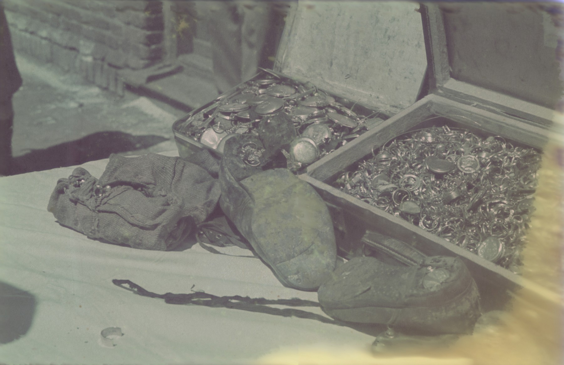 """A display of confiscated valuables, some buried in the heels of shoes, collected and sorted in the Pabianice labor camp/storage facility.  Original caption: Pabianice, """"Versteckte Werte"""" (hidden valuables), #32."""