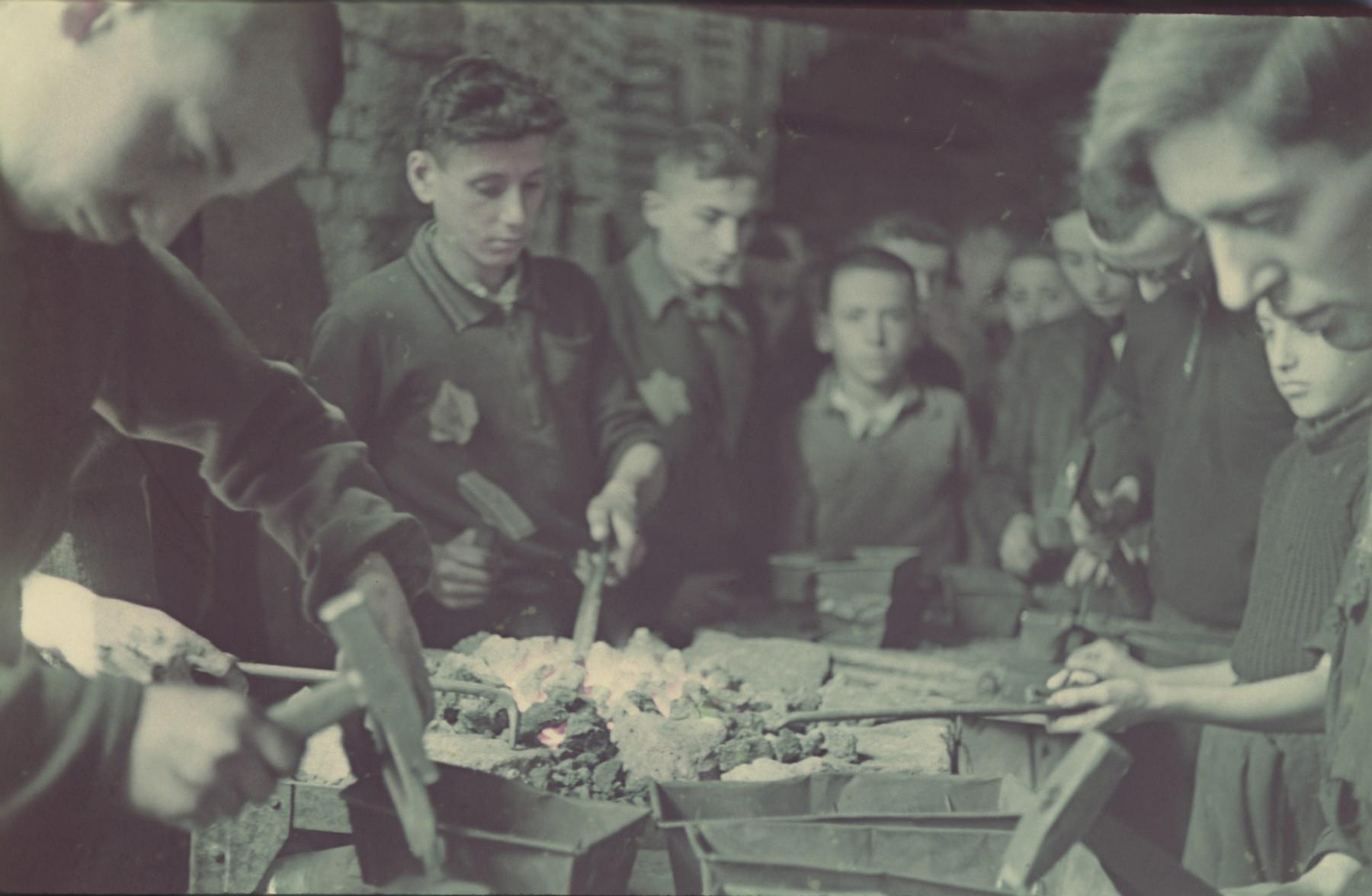 """Teenagers work in the Lodz ghetto metal workshop.  Original German caption: """"Litzmannstadt-Getto, Metallwerkstaette"""" (metal work place), #16."""