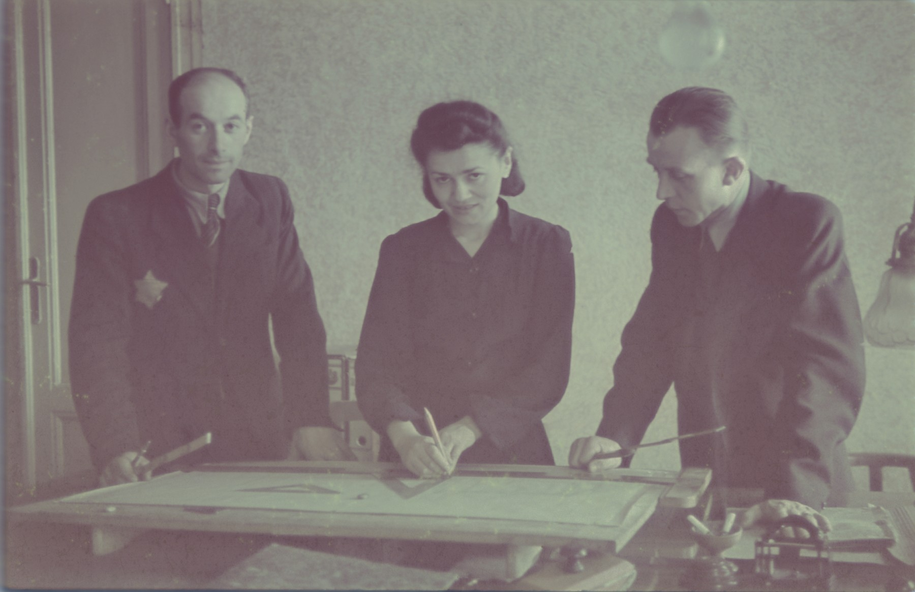 "Three designers look over plans in the office of the furniture factory.  Original German caption: ""Geto-Litzmannstadt, Architekten der Moebelfabrik""  (designers in the furniture factory), #209.  (Previous number 163 is crossed out.)"